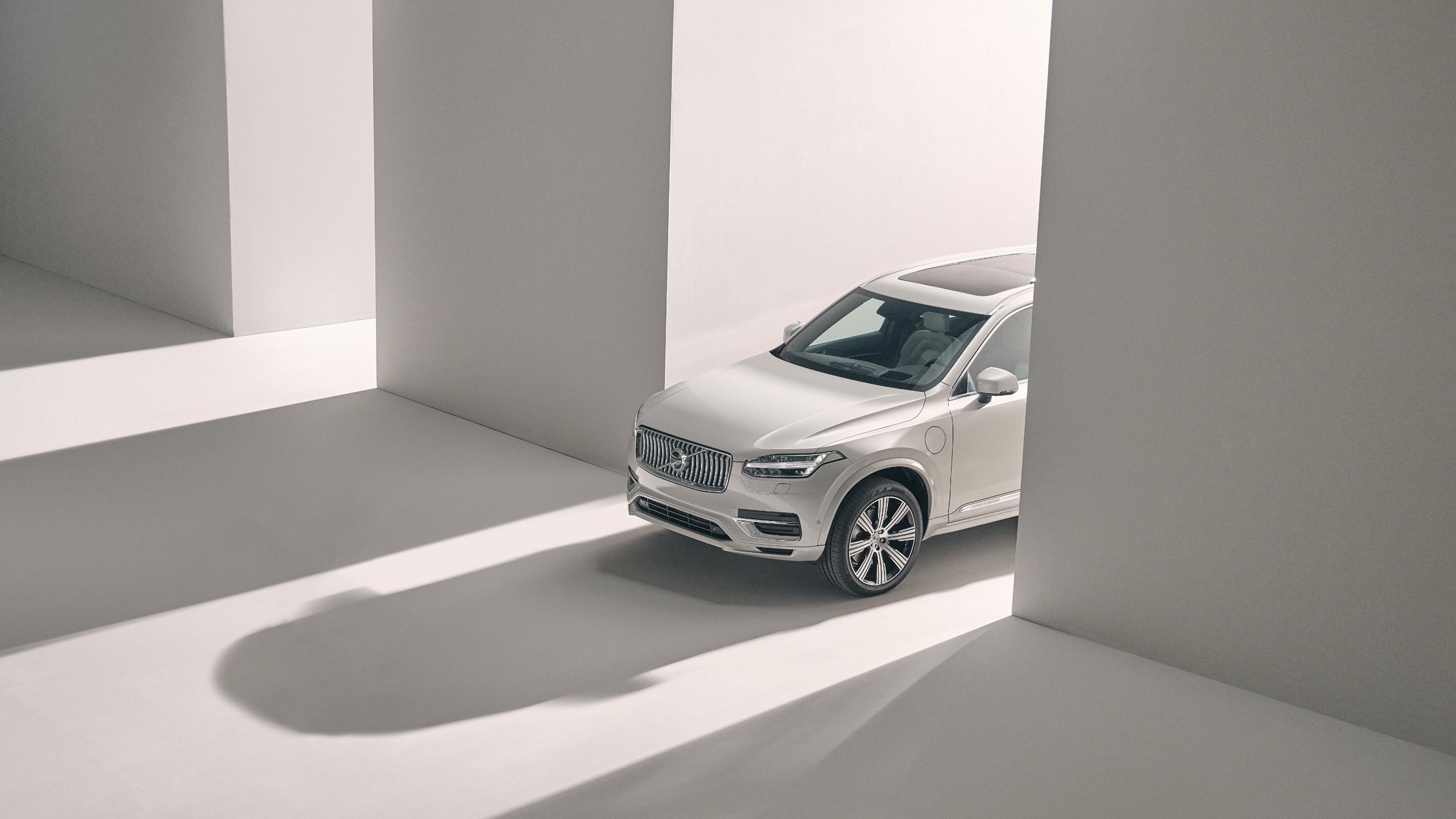 Schräge Aufsicht von oben auf einen stehenden Volvo XC90 Recharge in einer weißen Halle