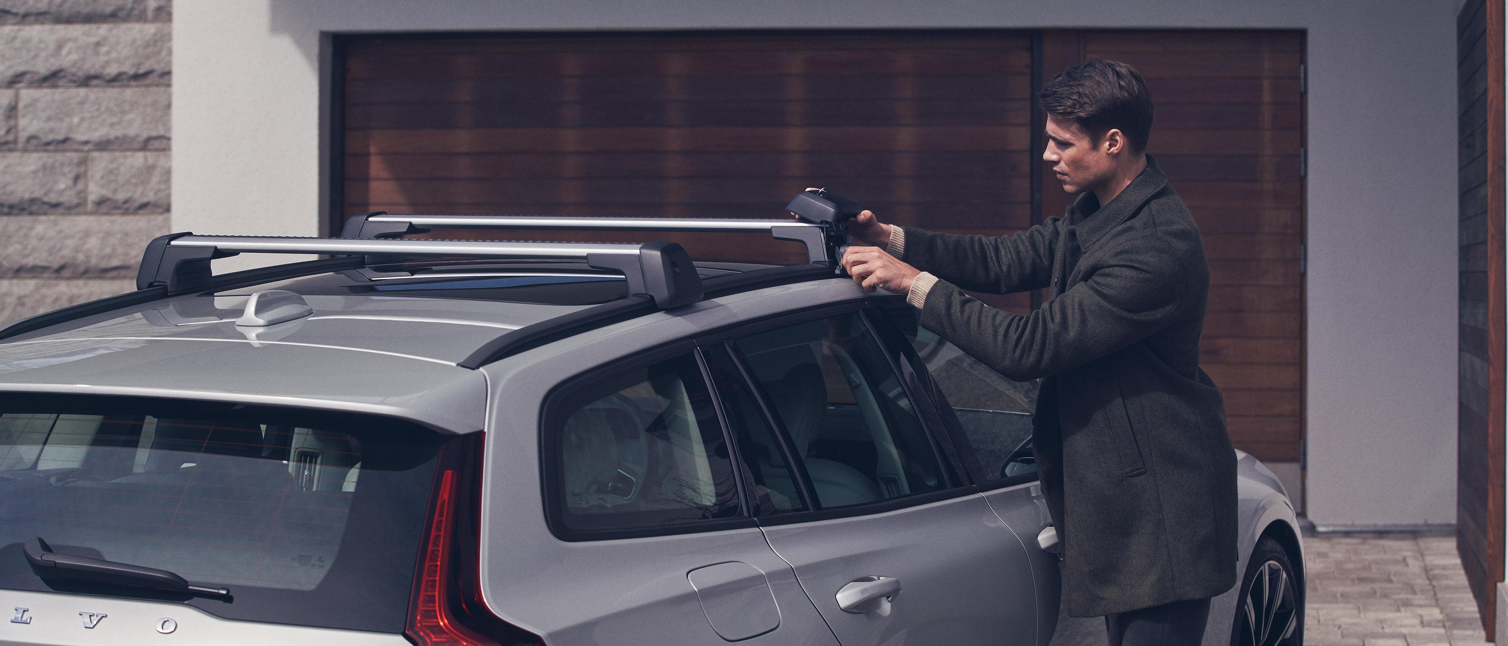 Ein Mann befestigt einen Lastenträger auf seinem Volvo.