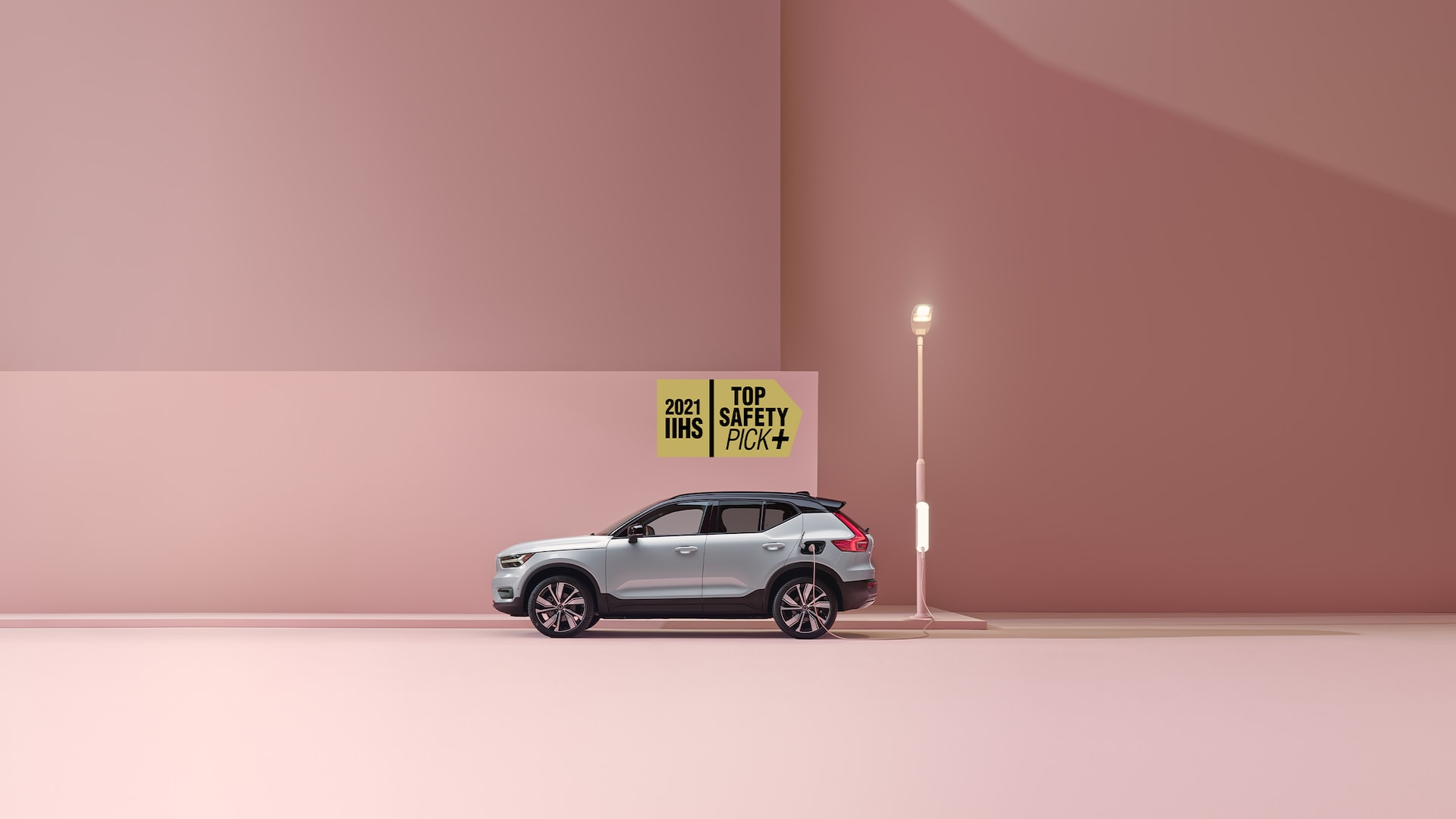 A white Volvo XC40 Recharge electric SUV charged in a pink city