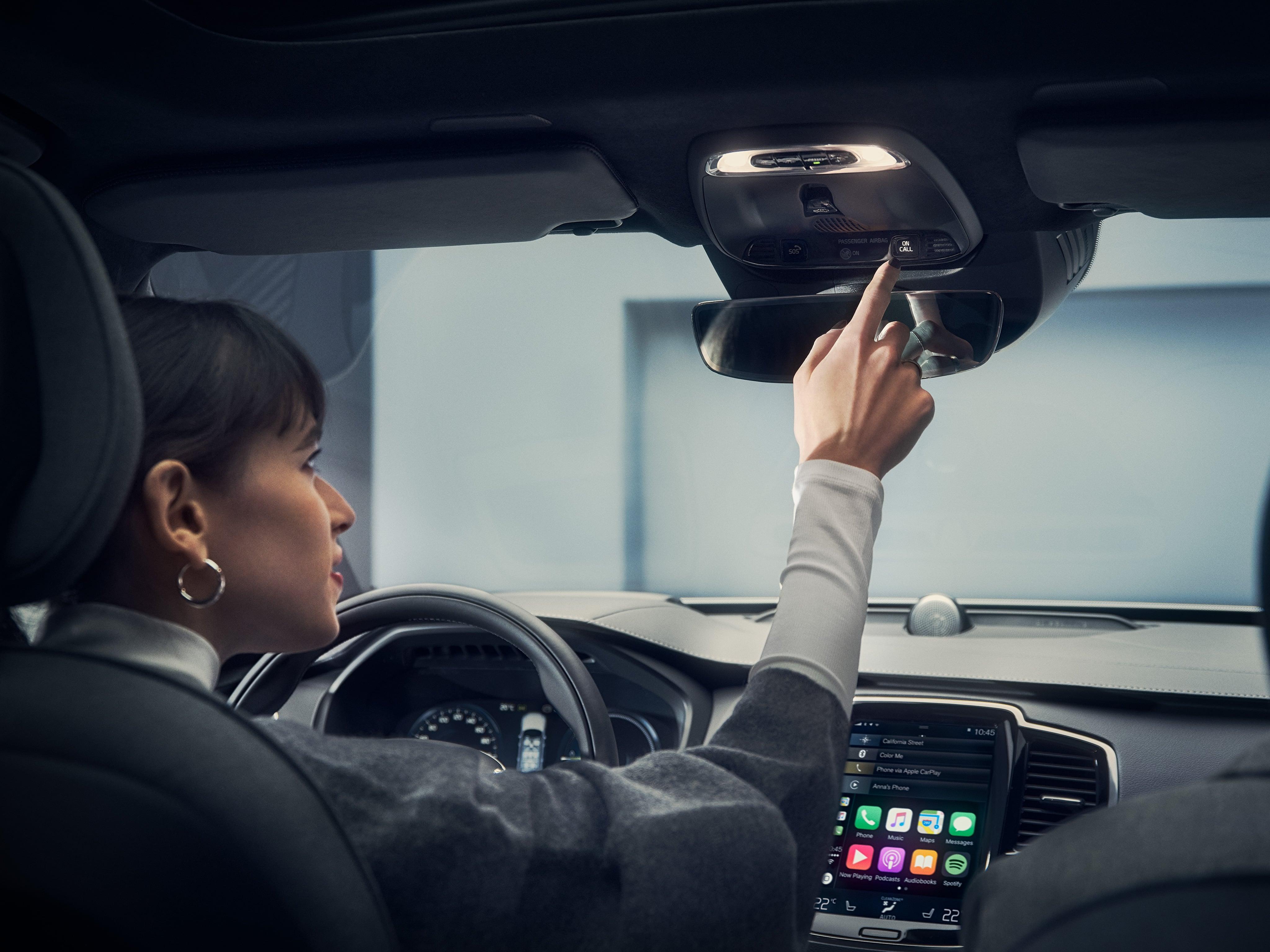 Una donna alla guida di una Volvo che preme un pulsante nel quadro di comando sopra lo specchietto retrovisore.
