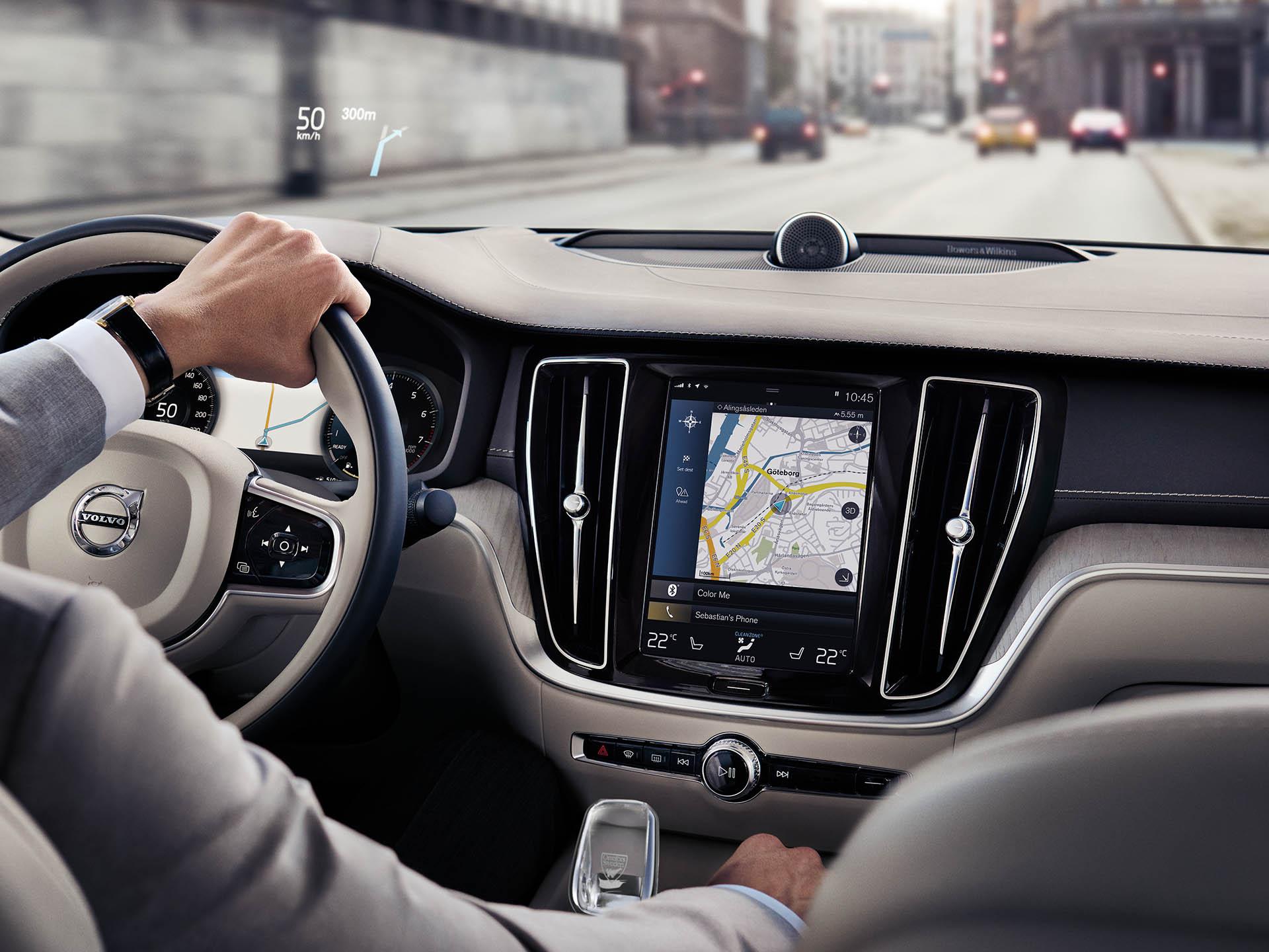 En el interior de un Volvo sedán, un hombre conduce por la carretera con ayuda del sistema de navegación