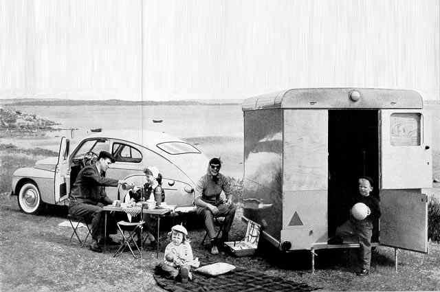 Una familia sentada junto a un Volvo y una caravana al lado del mar
