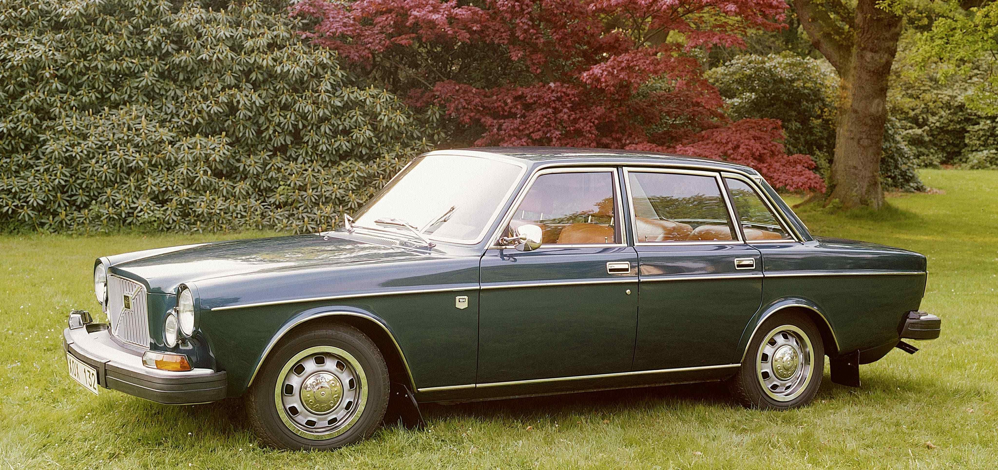 Un Volvo 164 de color verde aparcado en el cesped