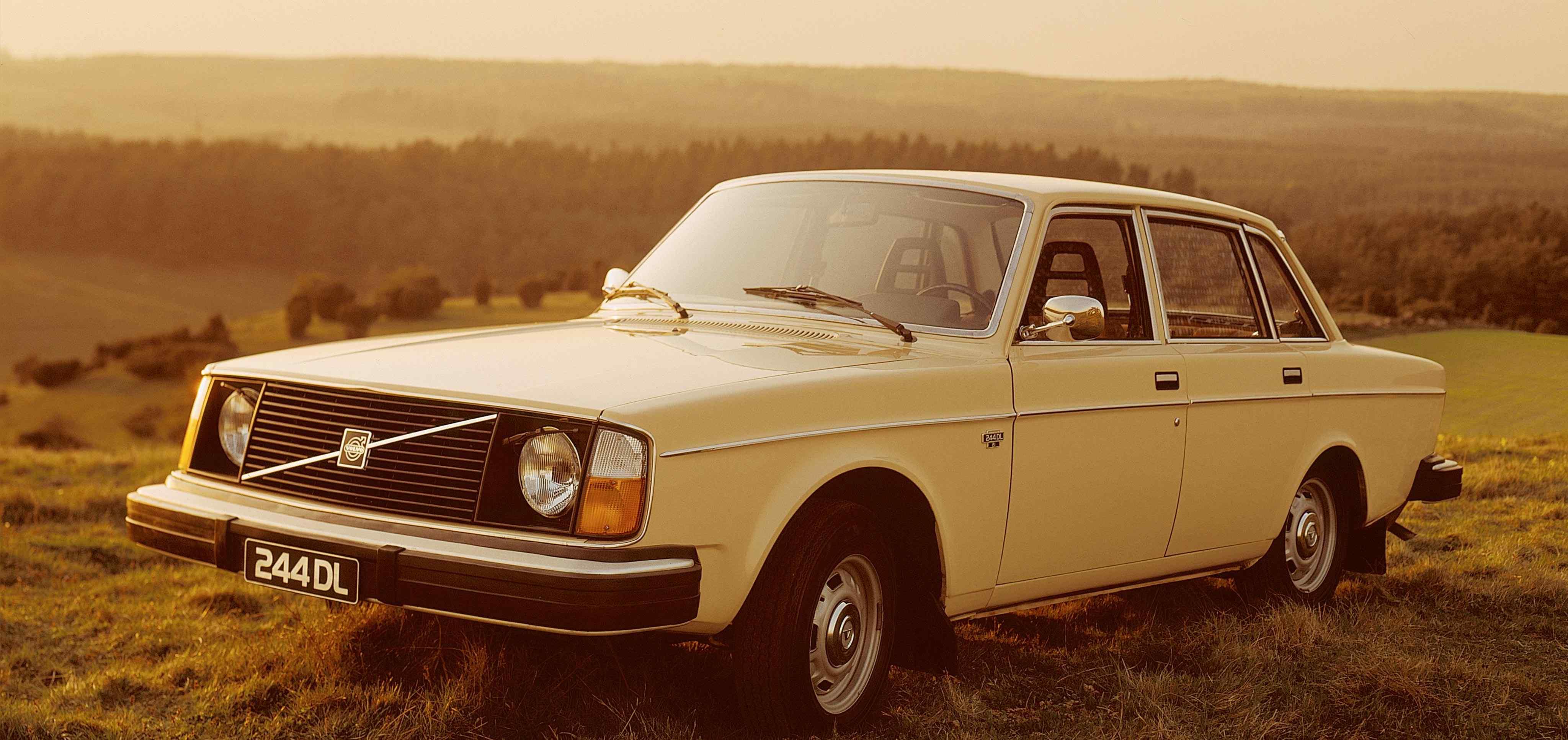 Un Volvo 244 color amarillo claro aparcado en lo alto de una colina con hierba