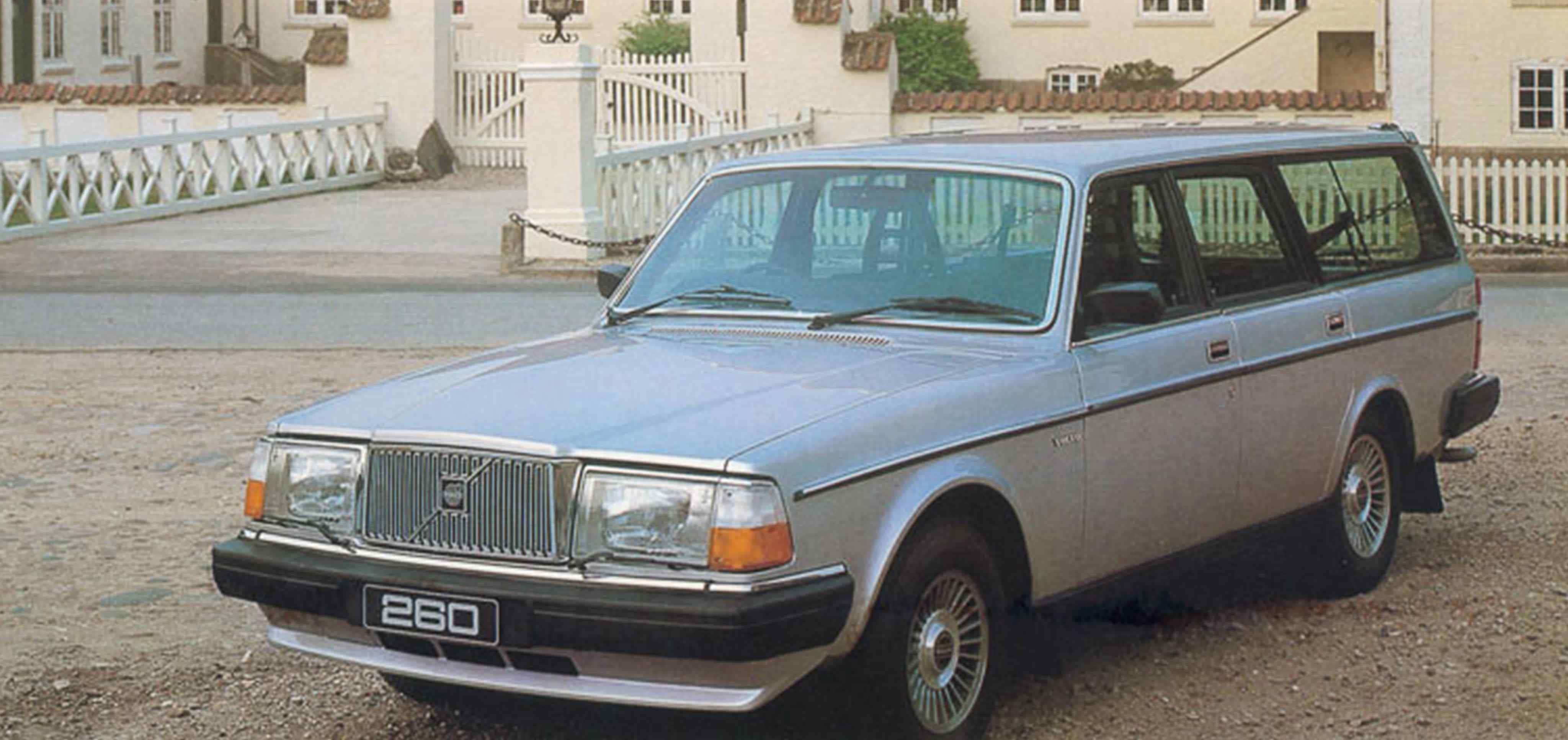 Un Volvo 260 de color azul claro aparcado a las puertas de una gran casa