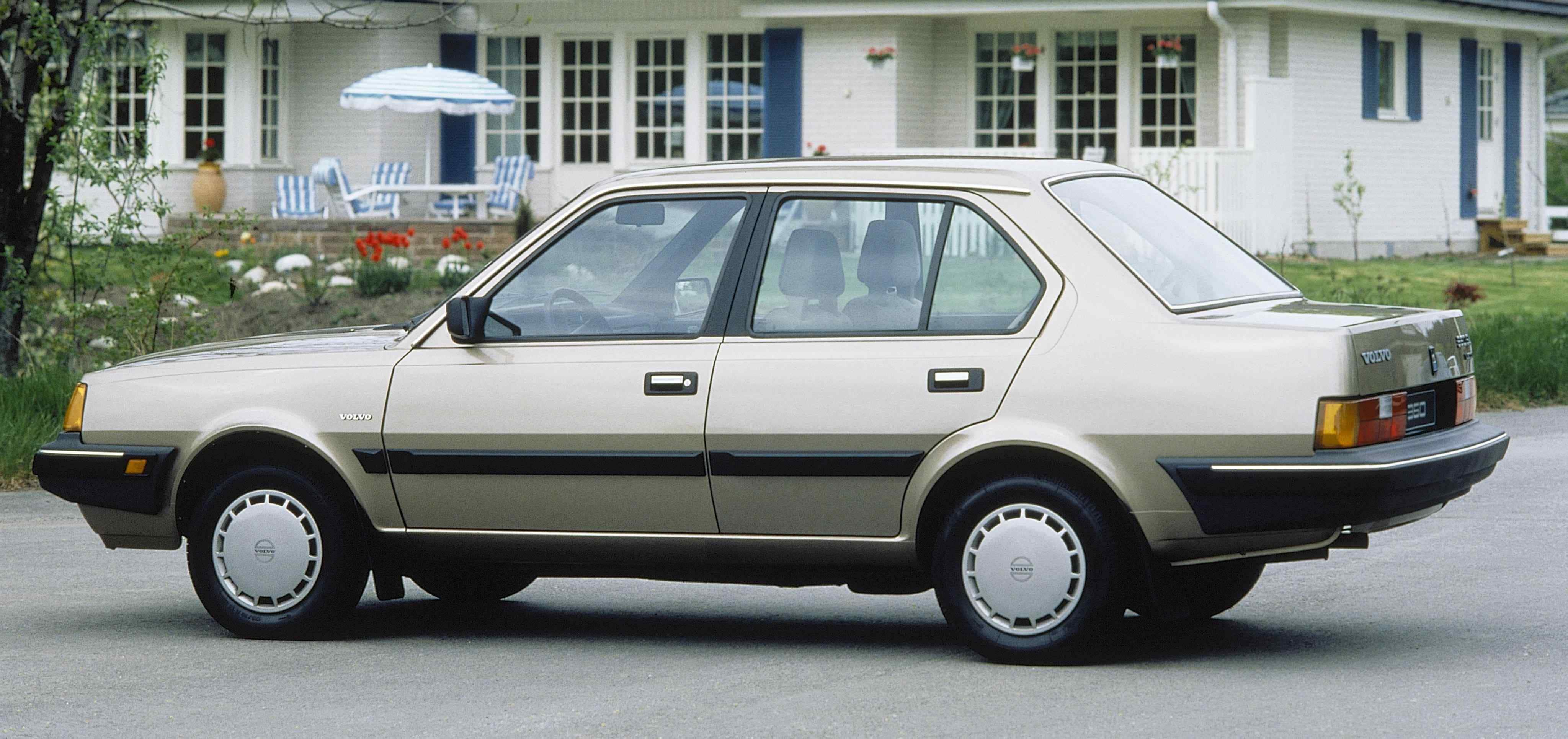 Un Volvo 360 sedán de color beige plateado aparcado delante de un edificio blanco