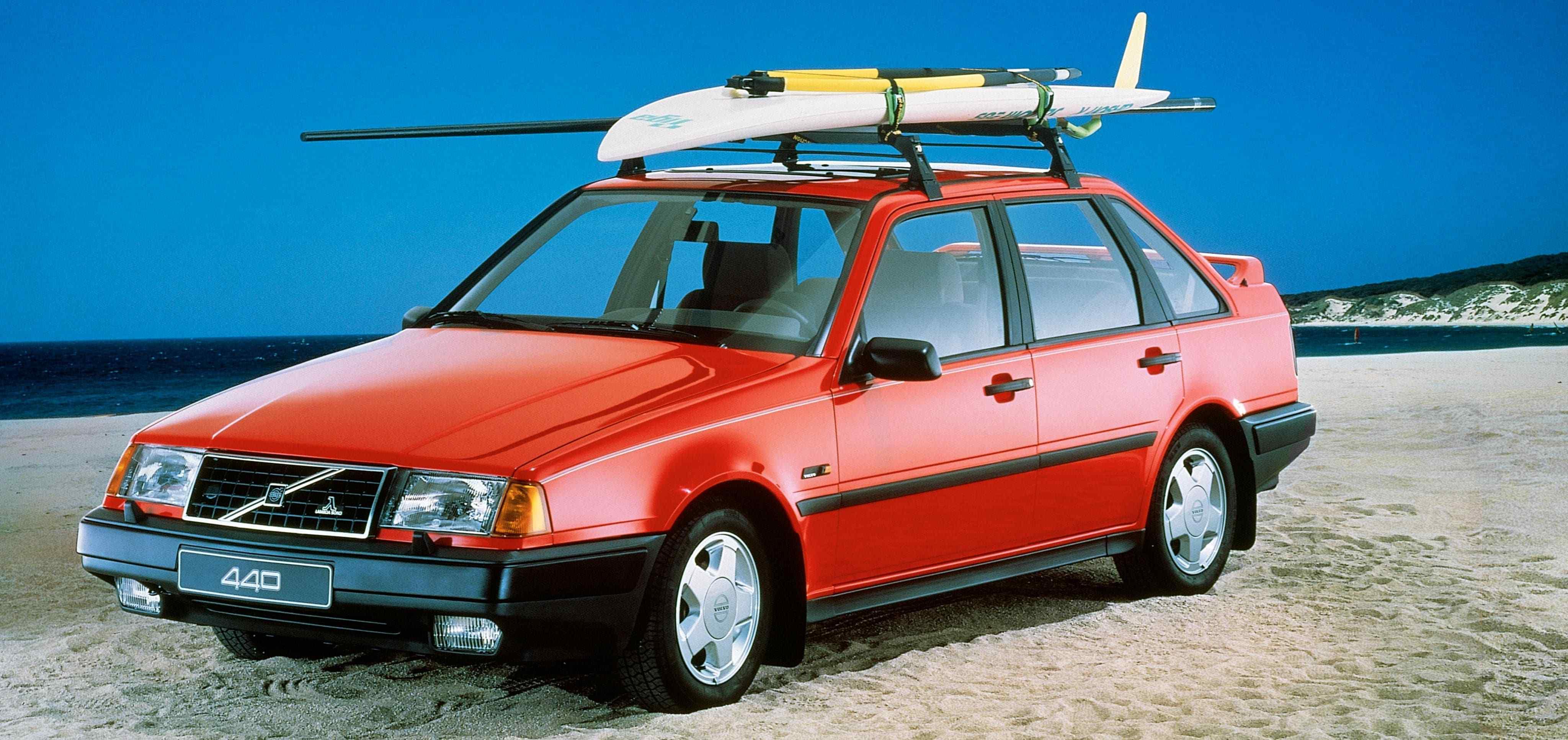 Un Volvo 440 de color rojo aparcado en la playa con una tabla de surf en el techo