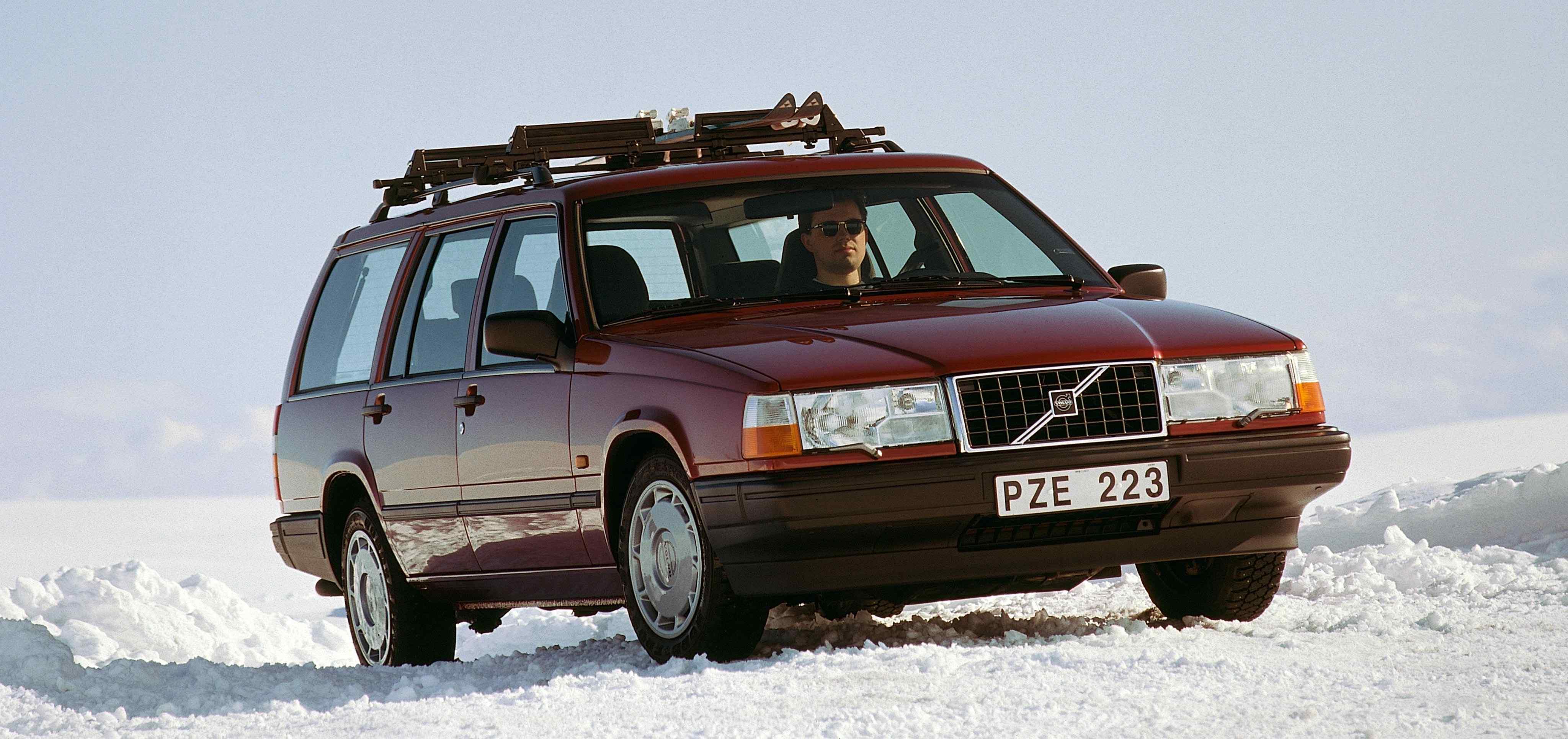 Un Volvo 940 estate color rojo burgundy  siendo conducido por una carretera cubierta de nieve