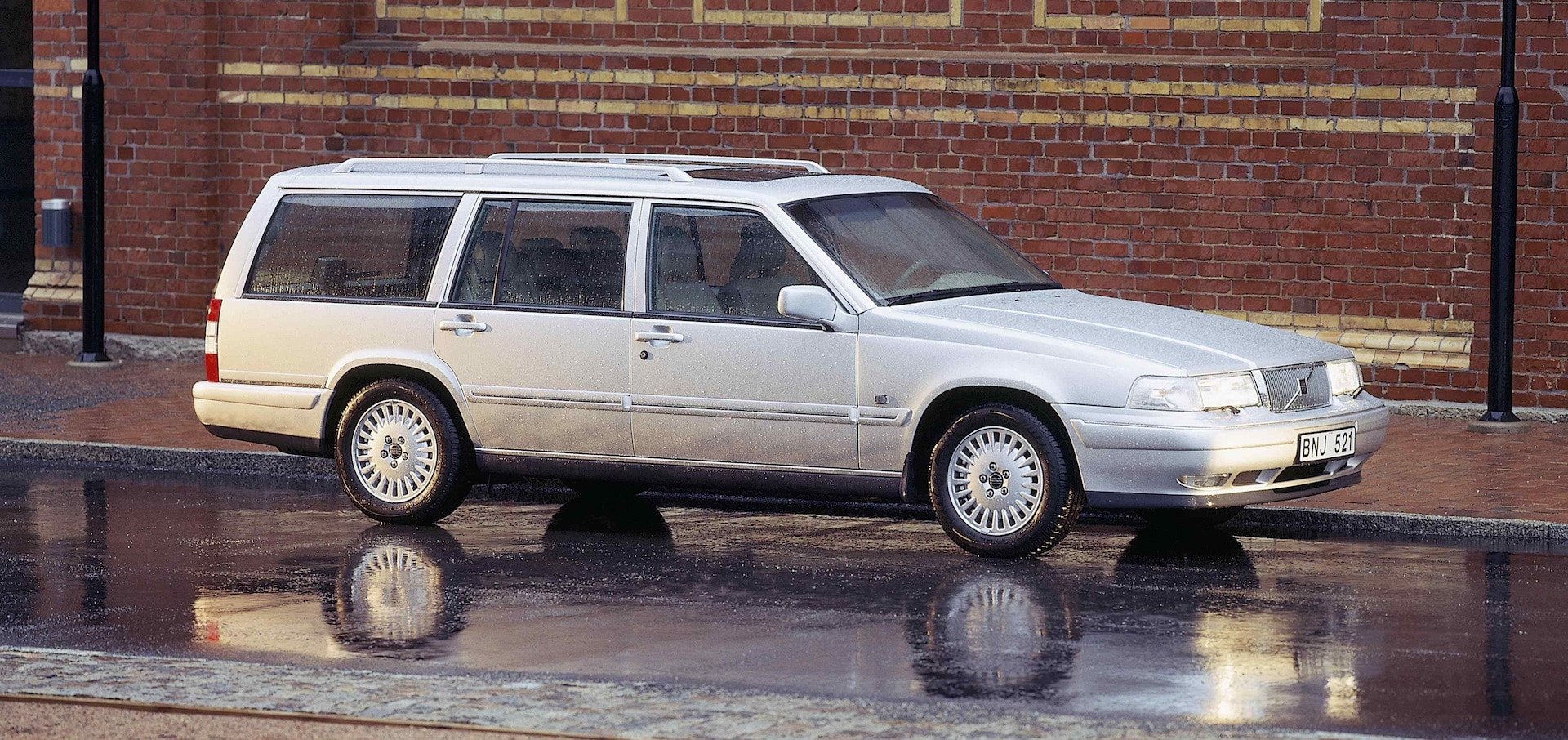 Un Volvo 960/V90 estate de color blanco aparcado en la calle delante de un muro de ladrillo rojo