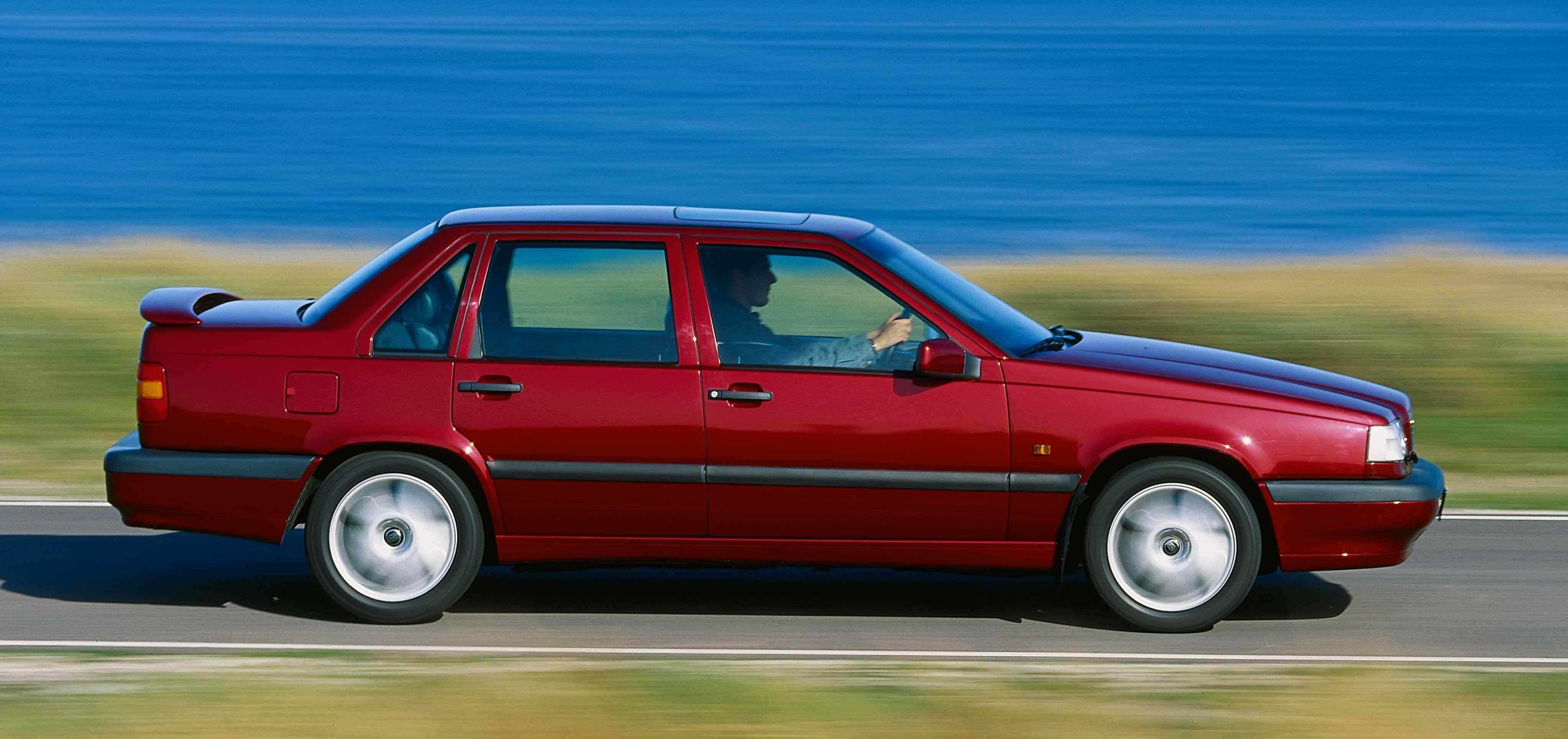 Un Volvo 850 sedán de color rojo conducido a lo largo de una carretera junto al mar