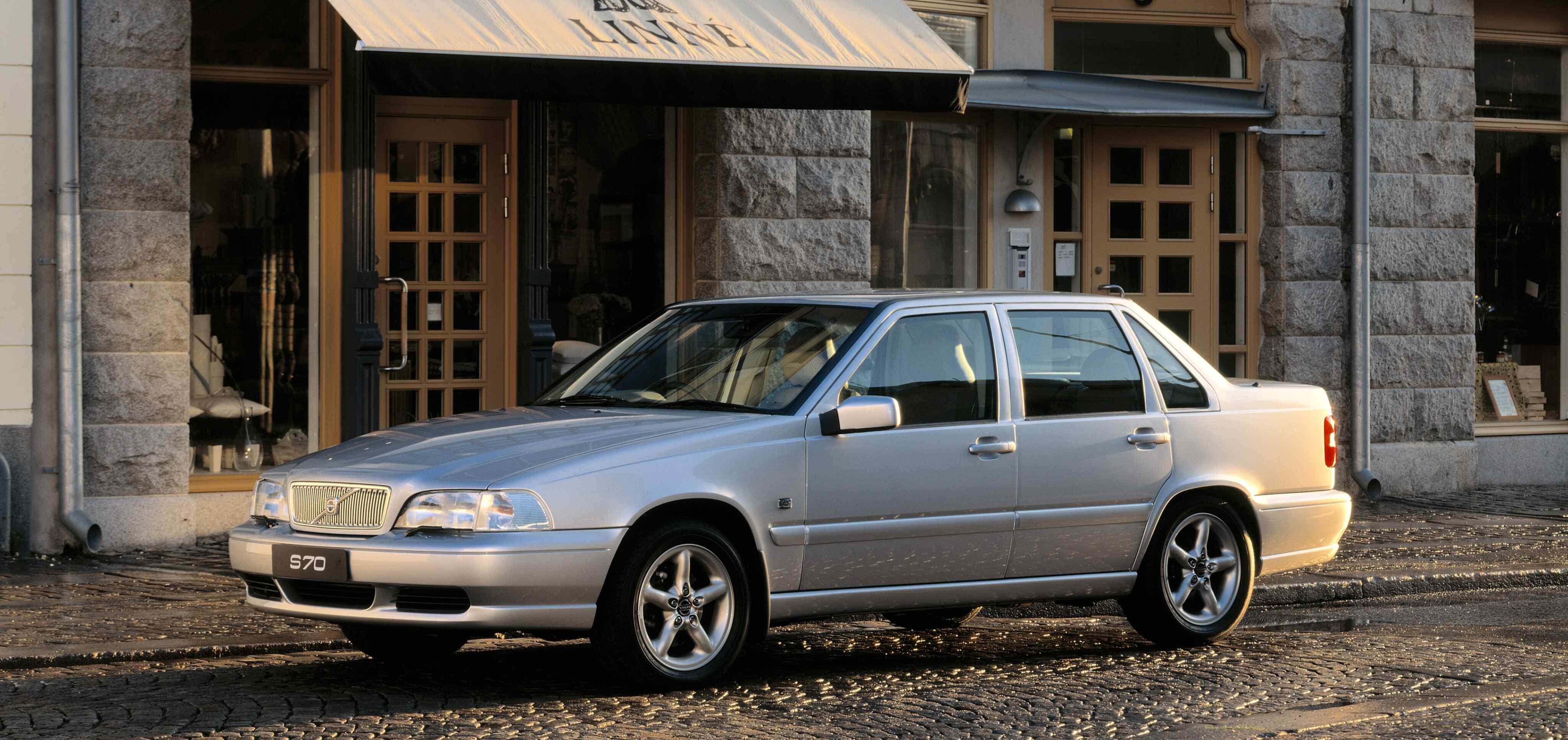 Un Volvo S70 plateado aparcado en una calle adoquinada