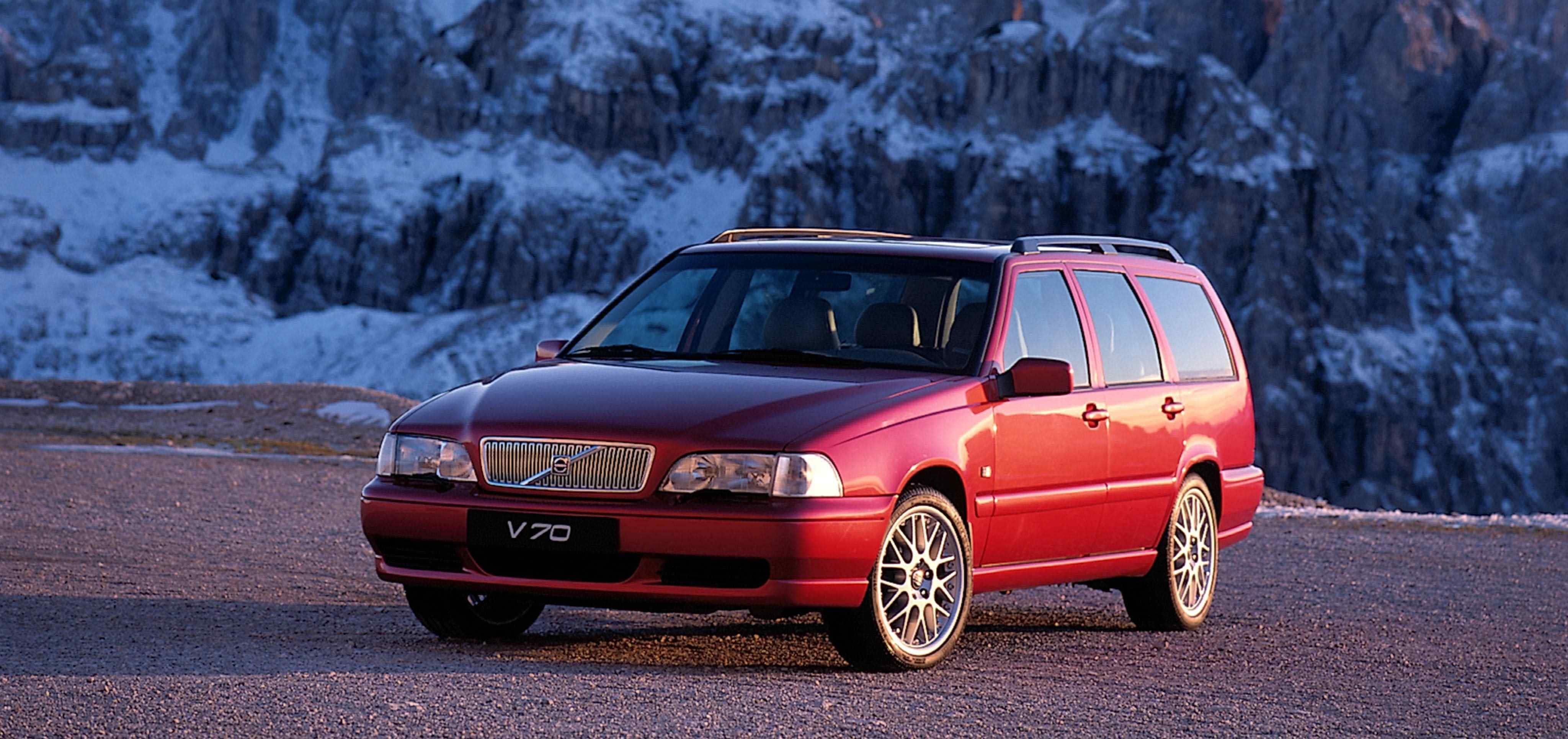 Un Volvo V70XC Classic de color rojo burgundy aparcado delante de unas rocas cubiertas por nieve
