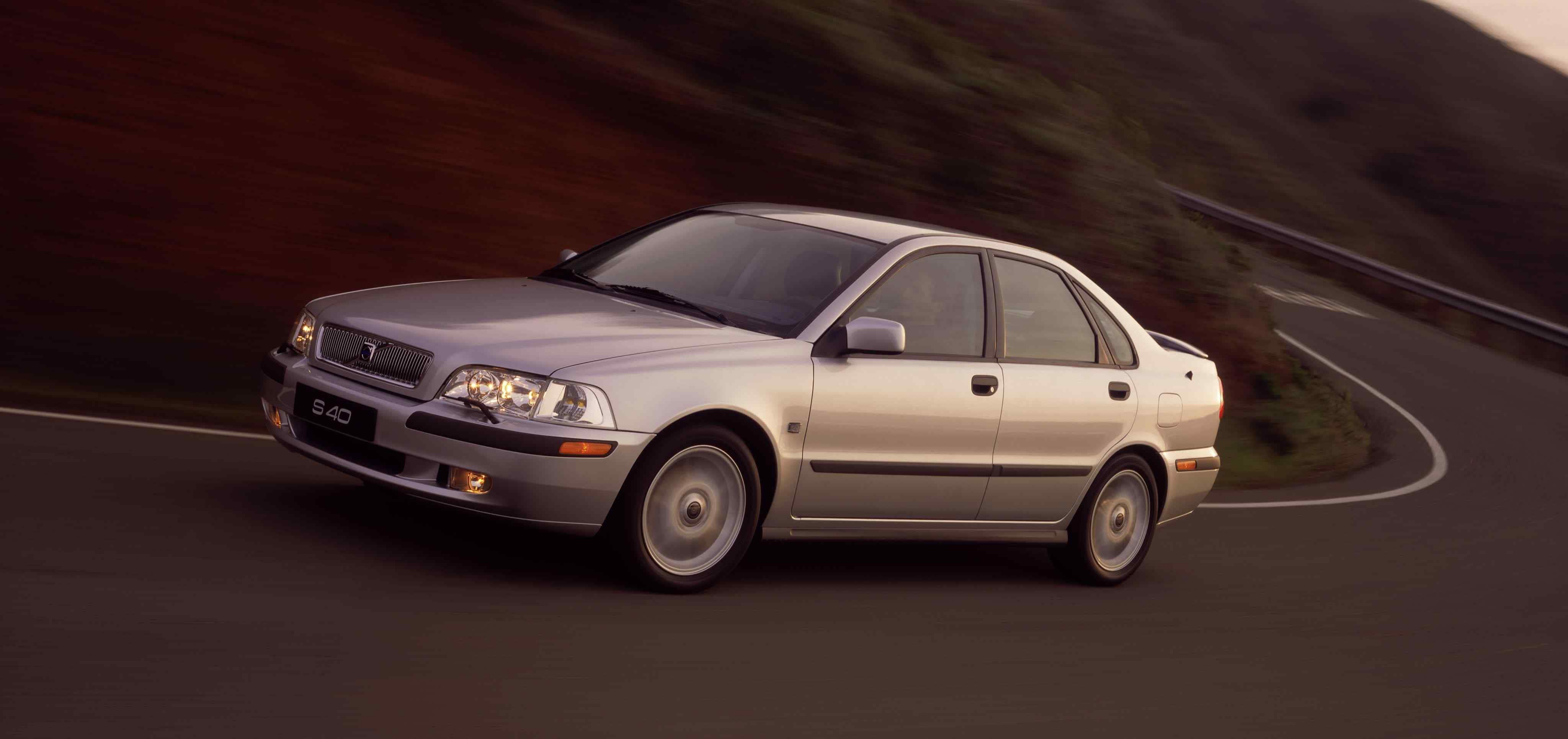 Un Volvo S40 primera generación de color plata junto a una carretera en curva