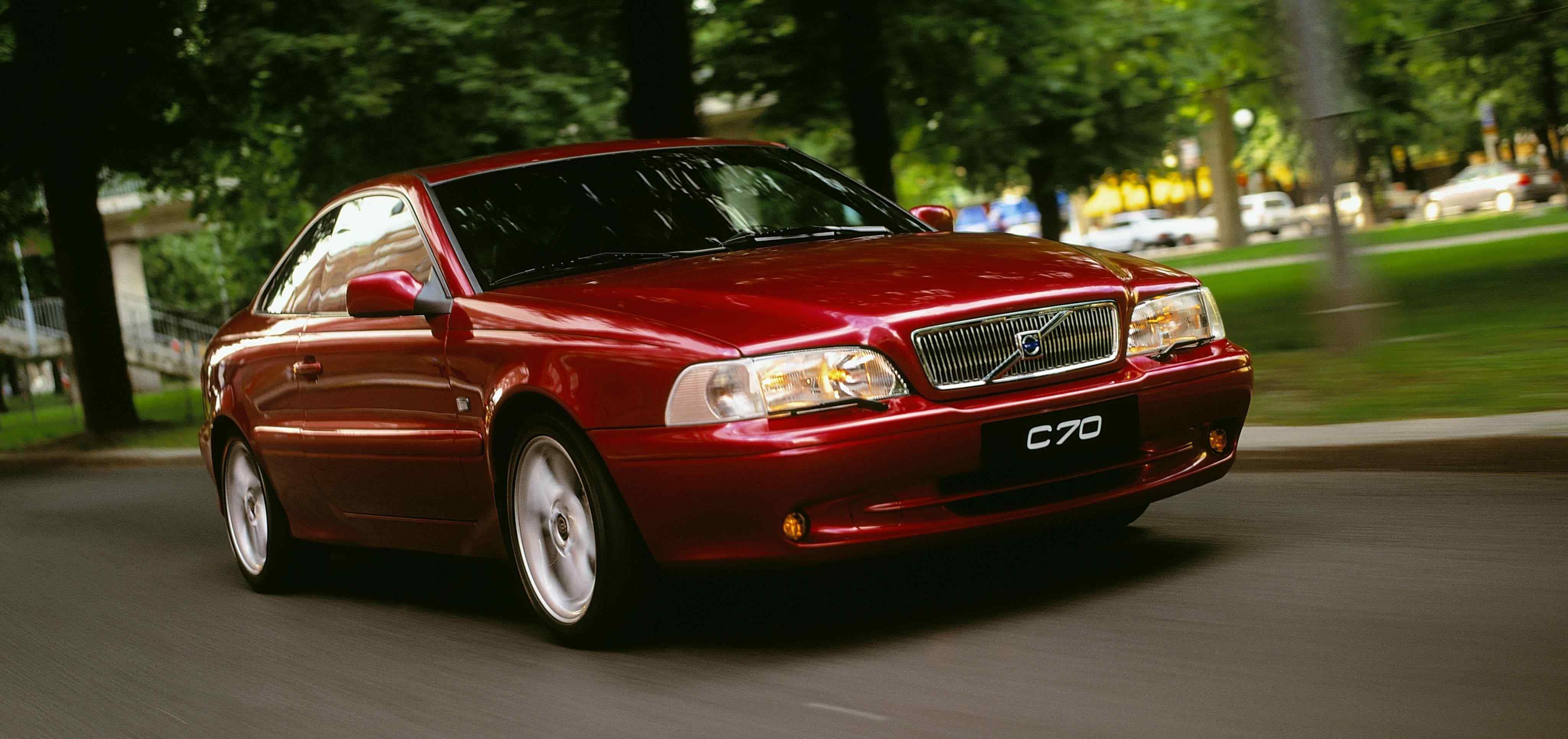 Un Volvo C70 coupe color rojo burgundy siendo conducido a lo largo de una carrereta con árboles