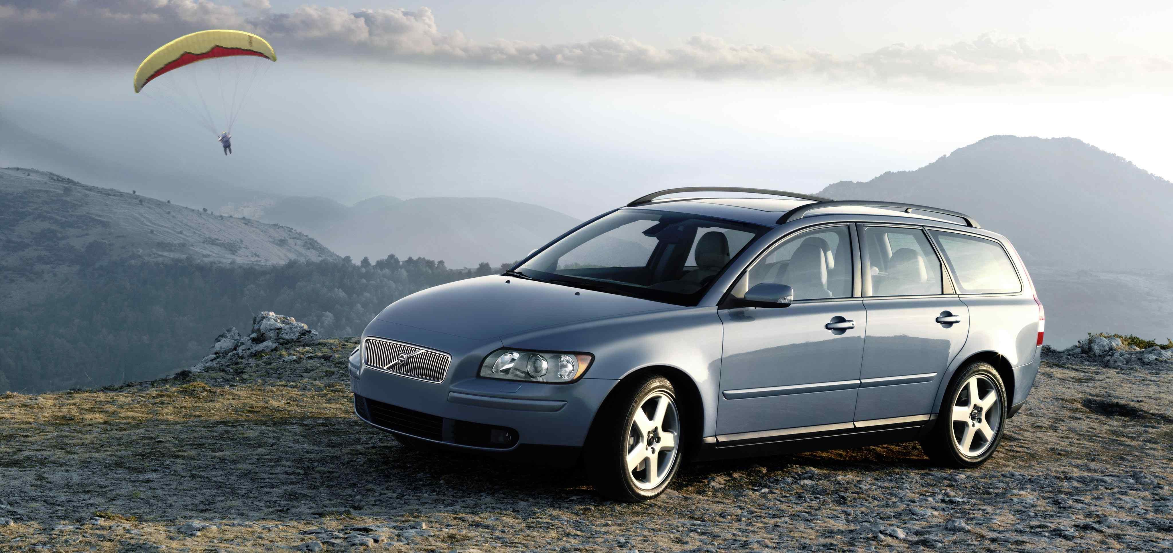 Un Volvo V50 de color azul claro aparcado junto a una carretera en la cima de una colina con montañas en segundo plano