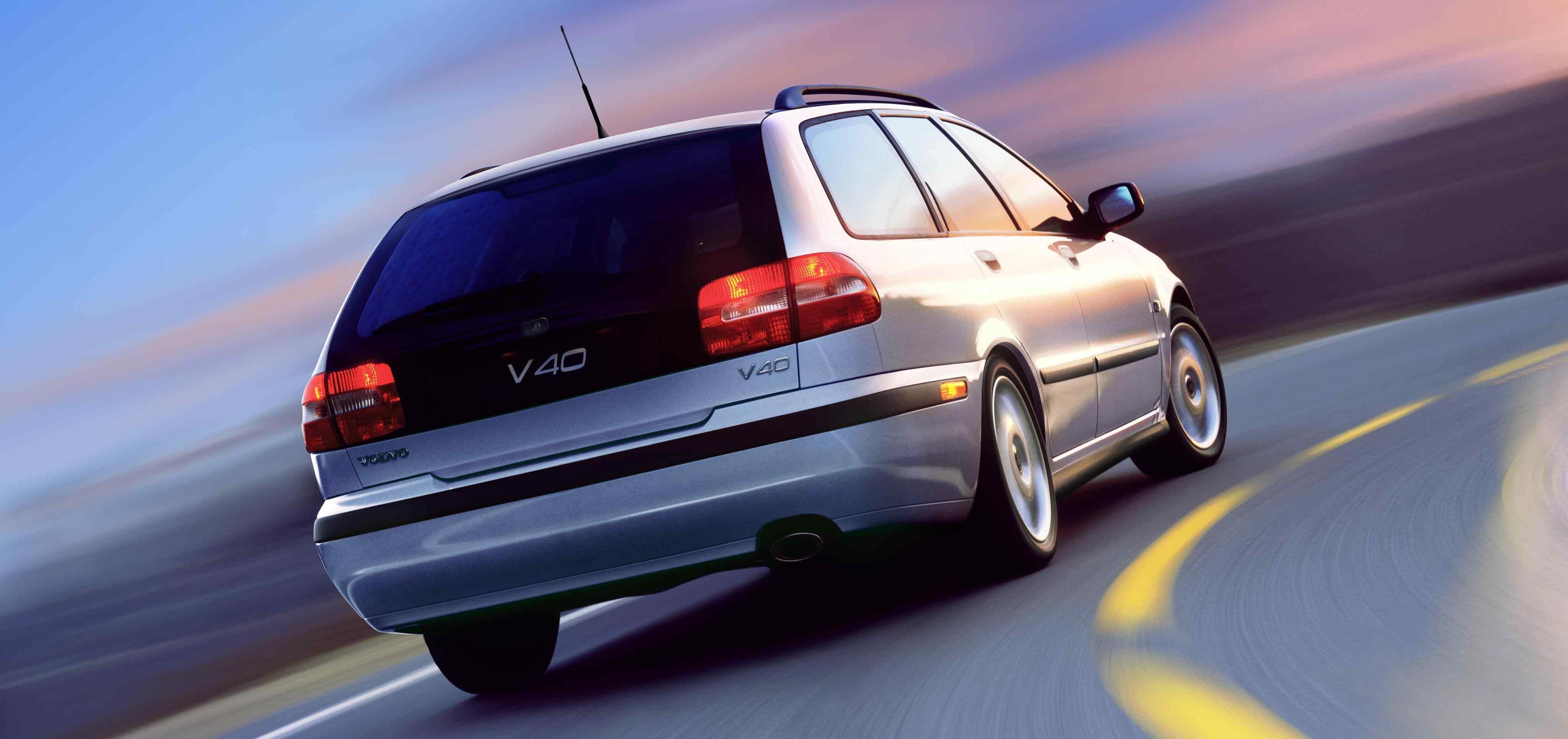 Un volvo V40 primera generación de color plata junto a una carretera en curva visto por detrás