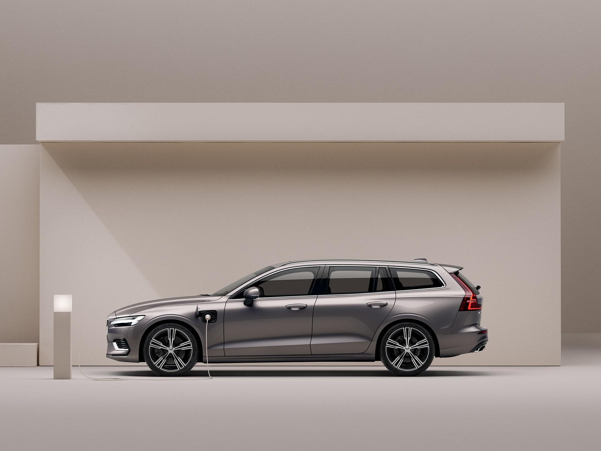 Egy bézs Volvo V60 Recharge töltés alatt bézs környezetben.