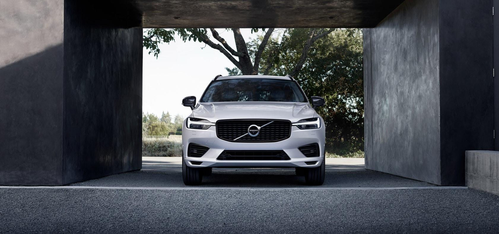 Naast een betonnen gebouw staat een witte Volvo XC60 geparkeerd