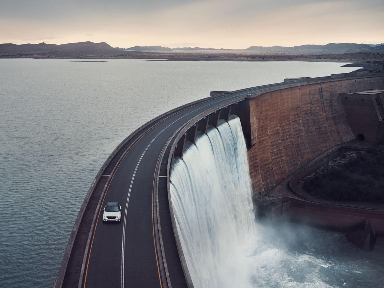 Un SUV Volvo roulant sur une route qui longe un barrage d'un lac de retenue.