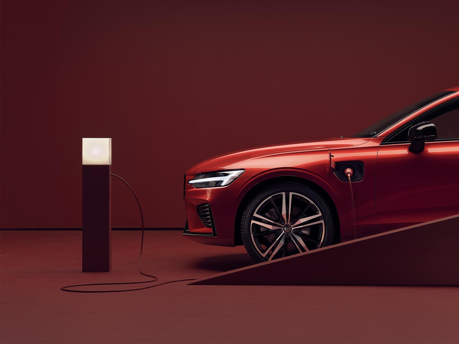 Berline Volvo rouge en stationnement branchée sur une borne de recharge