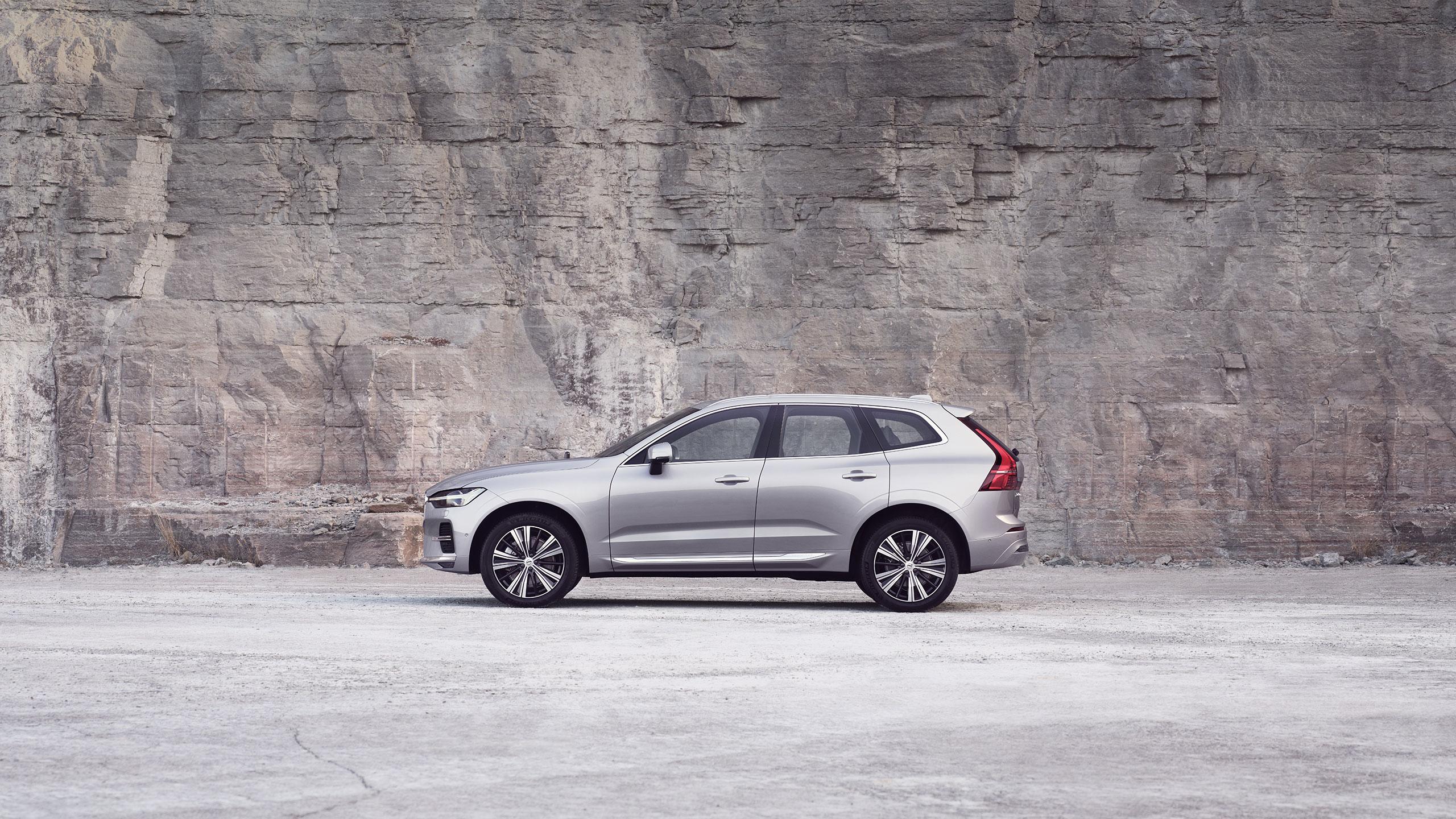 Srebrni Volvo XC60 stoji ispred kamenog zida.