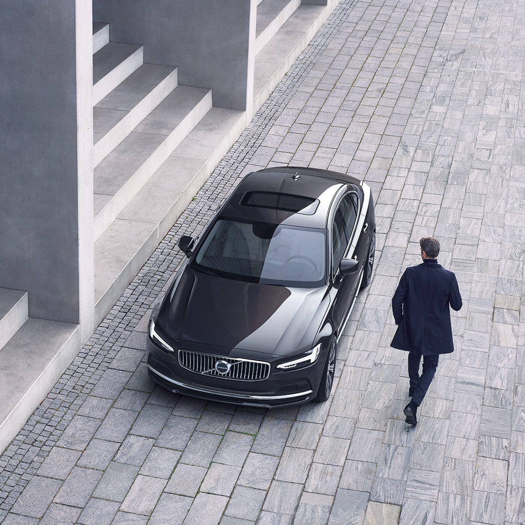 A Volvo S90 is parked in front of a set of stairs, a man walks towards the car.