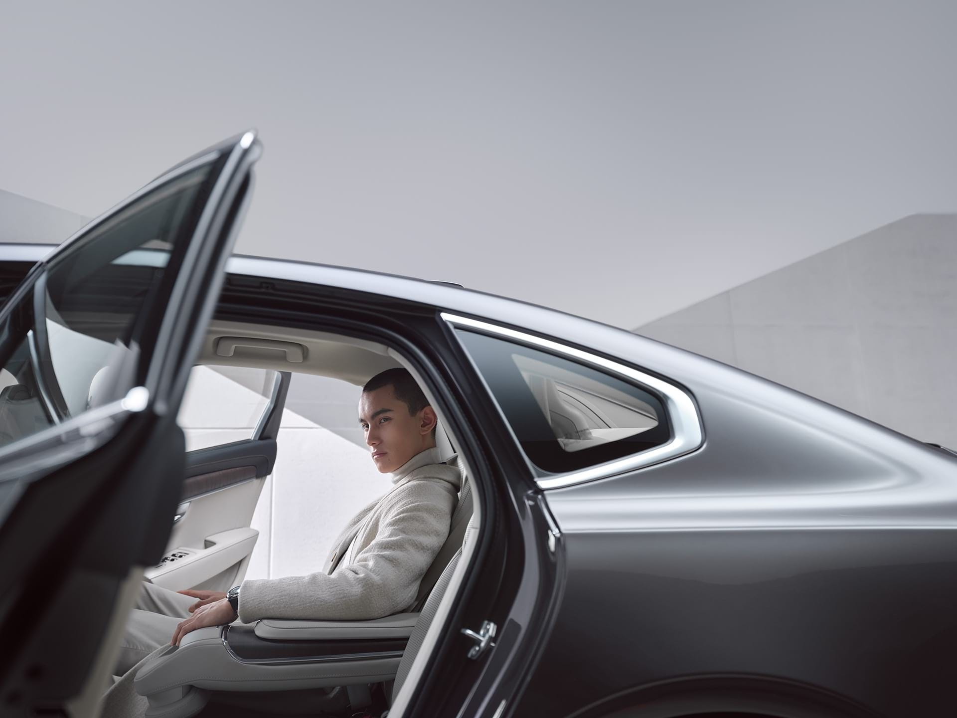 رجل يجلس في المقعد الخلفي لفولفو S90 Recharge.