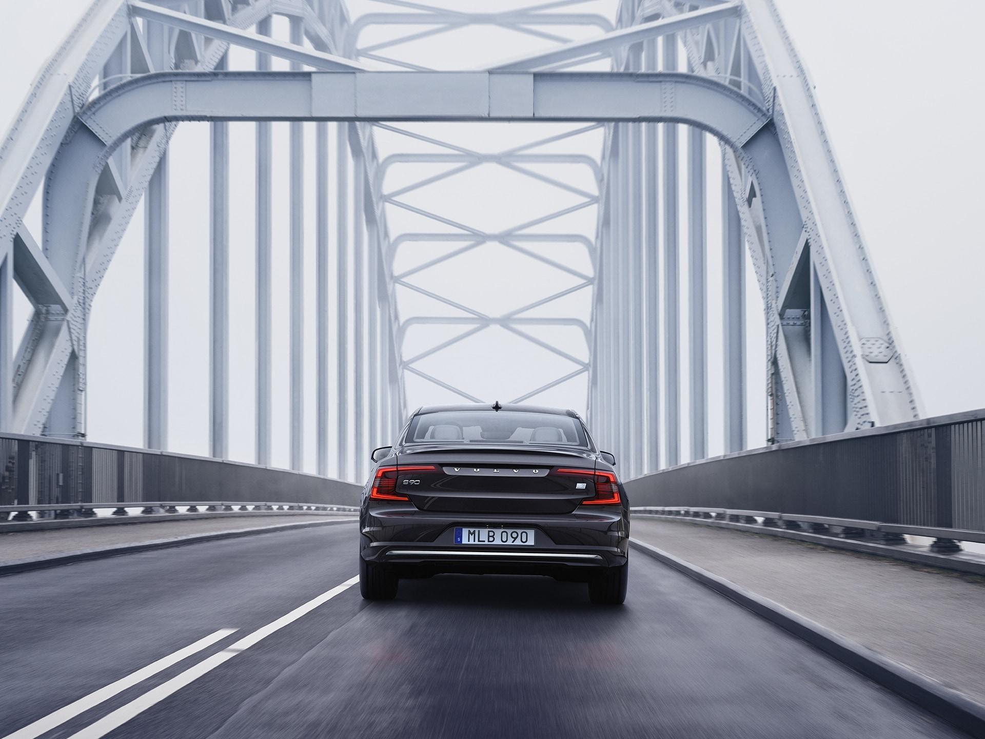 فولفو S90 Recharge تسير على جسر في يوم غائم.