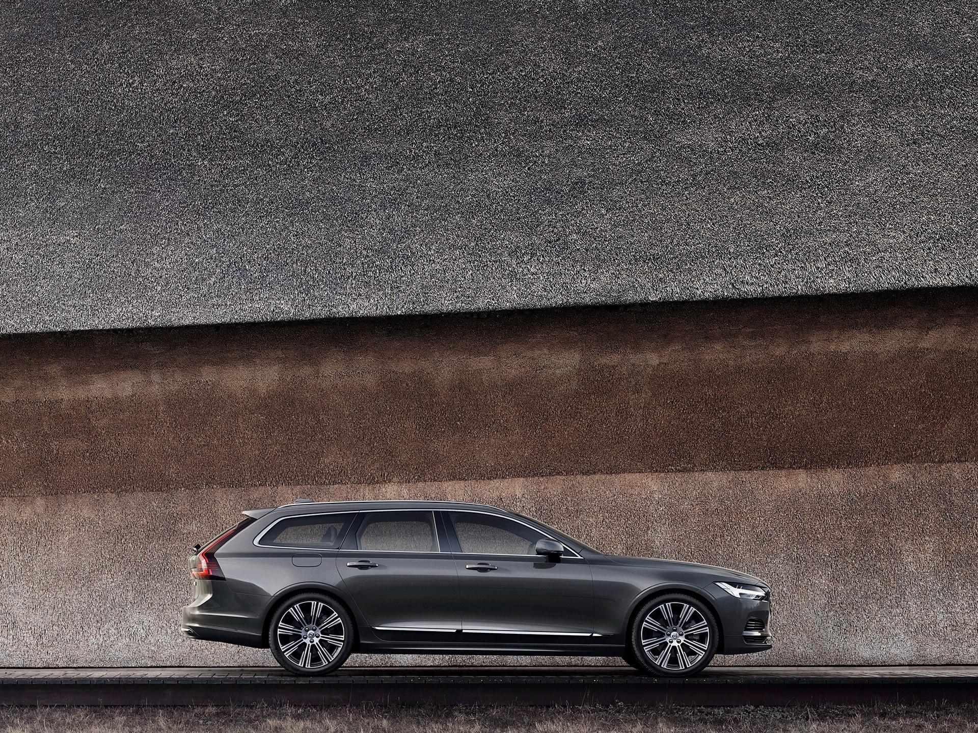 Ein dunkelgrauer Volvo V90, der vor einer Wand geparkt ist.