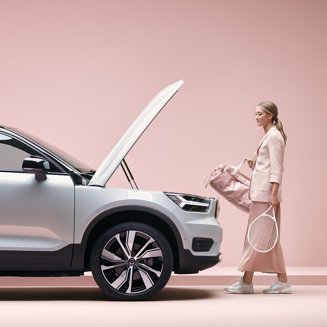 Une jeune fille blonde avec un sac de sport et une raquette de tennis à la main en route vers sa Volvo XC40 Recharge.