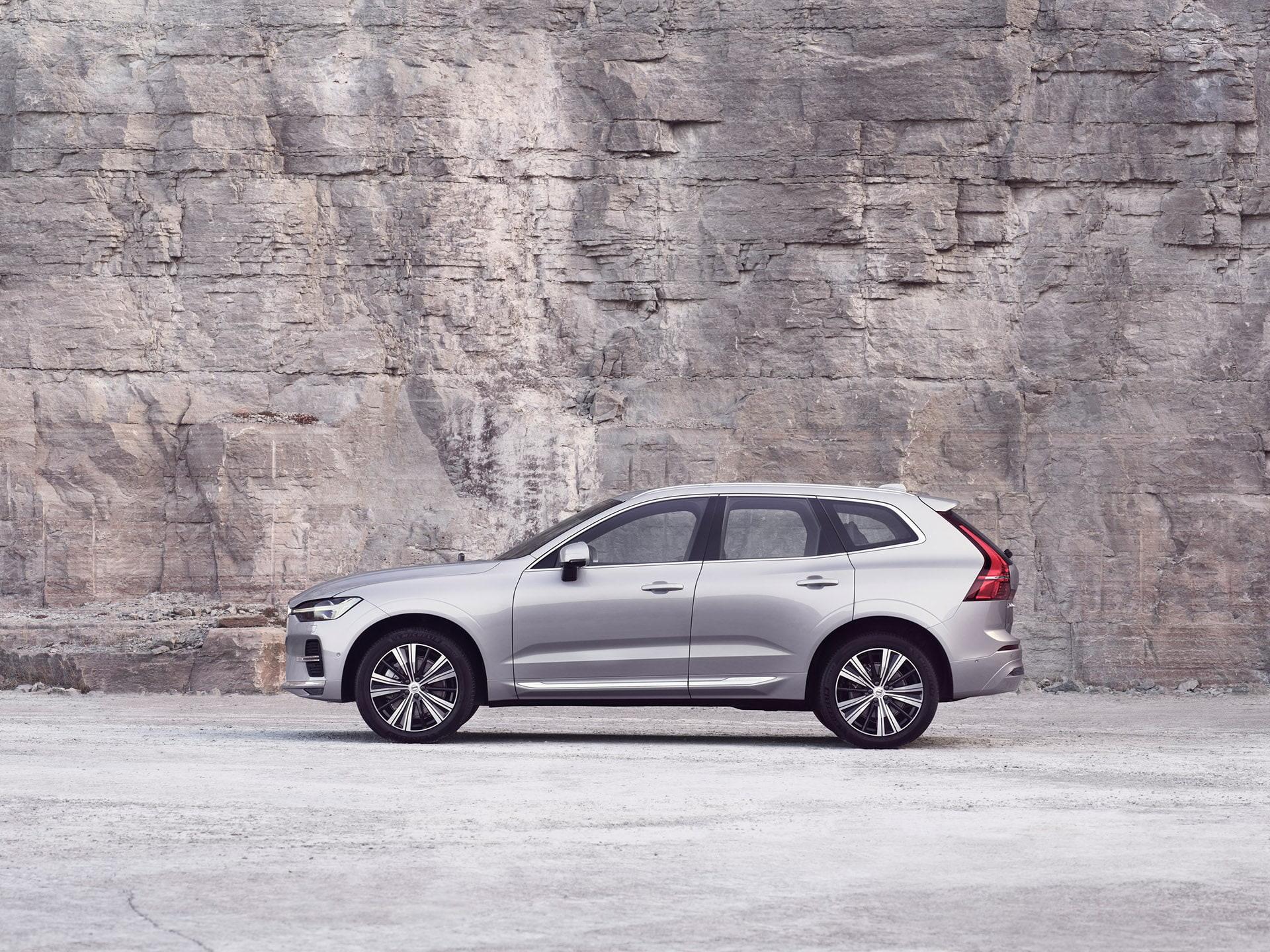 فولفو XC60 فضية تقف أمام جدار صخري.
