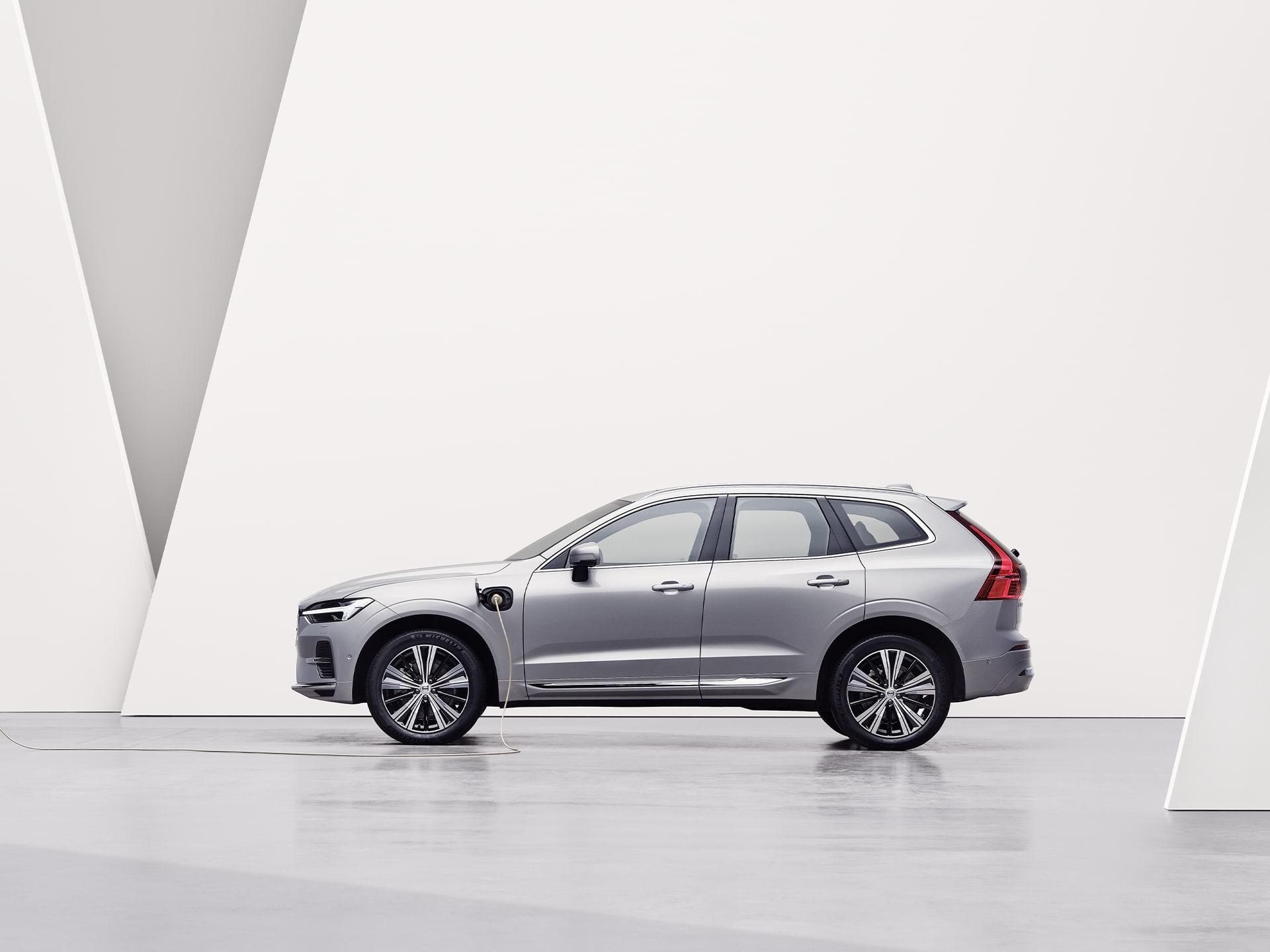 Une Volvo XC60 Recharge couleur argent, en charge dans un environnement blanc.