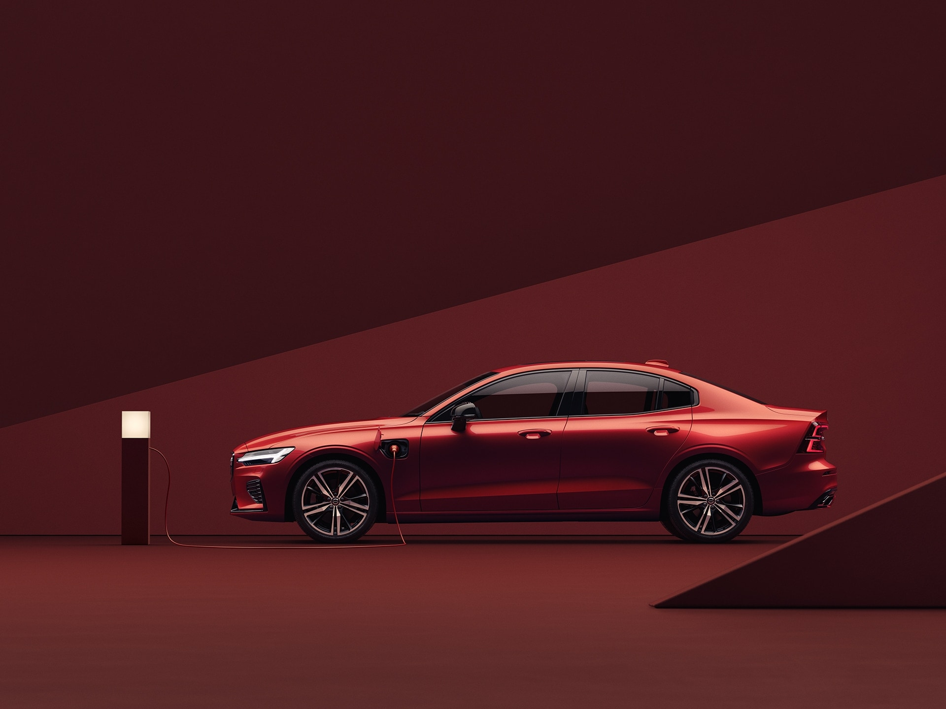 Petite berline sportive Volvo S60 Recharge rouge, en charge dans un environnement rouge.