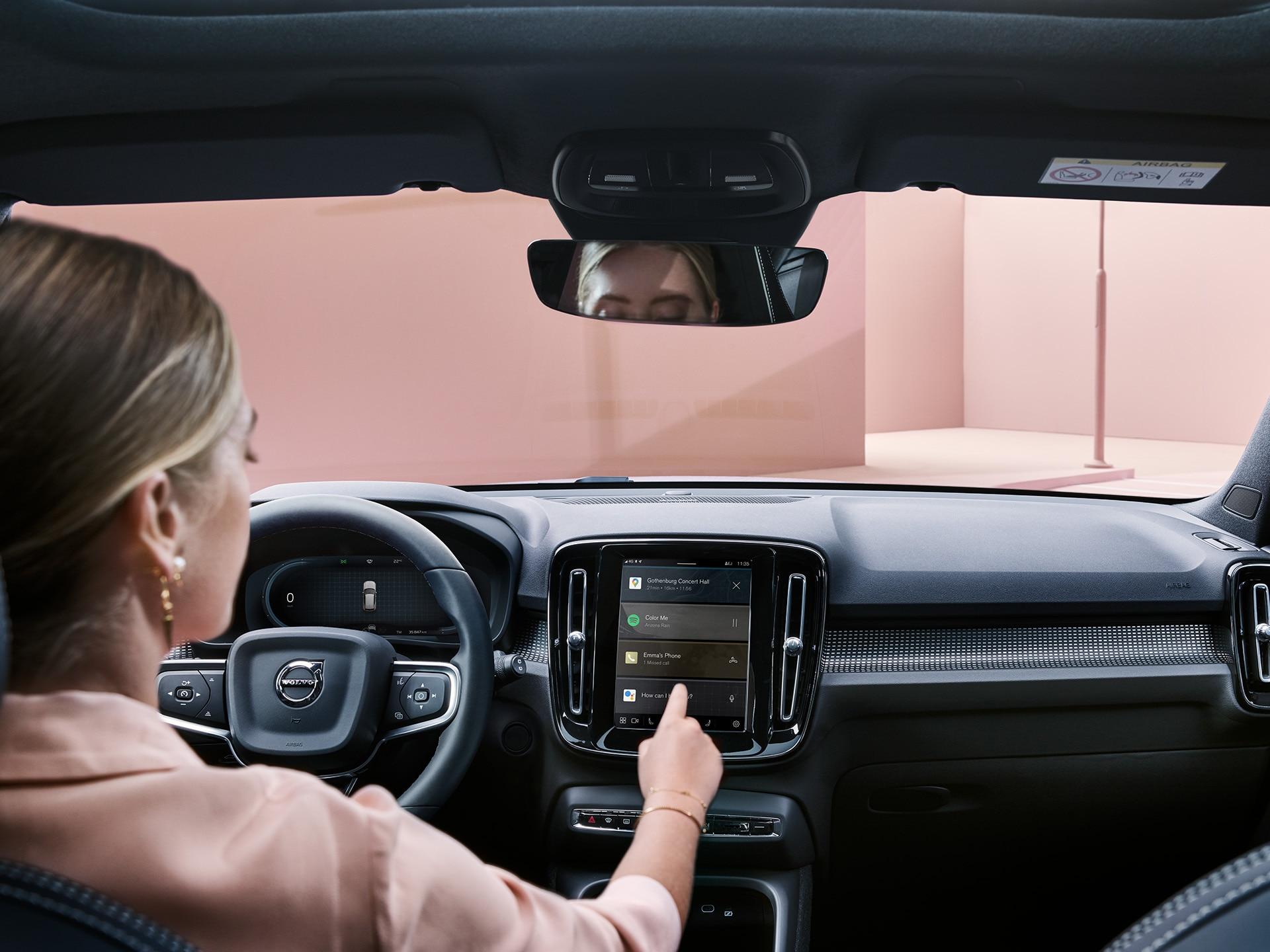 Një grua brenda një makine Volvo XC40 Recharge, duke përdorur sistemin e lidhjeve
