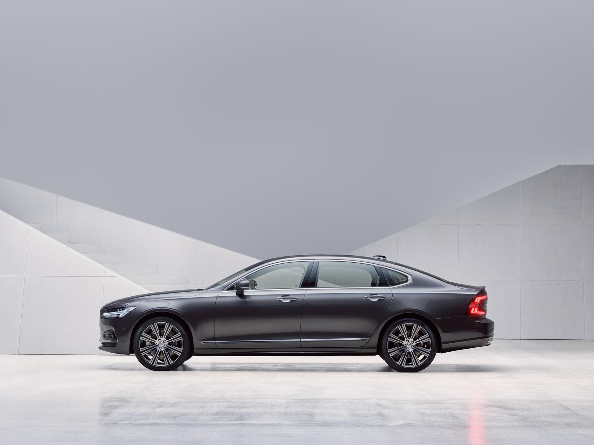 Një Volvo S90 ngjyrë e errët e parkuar përpara një muri ngjyrë gri.