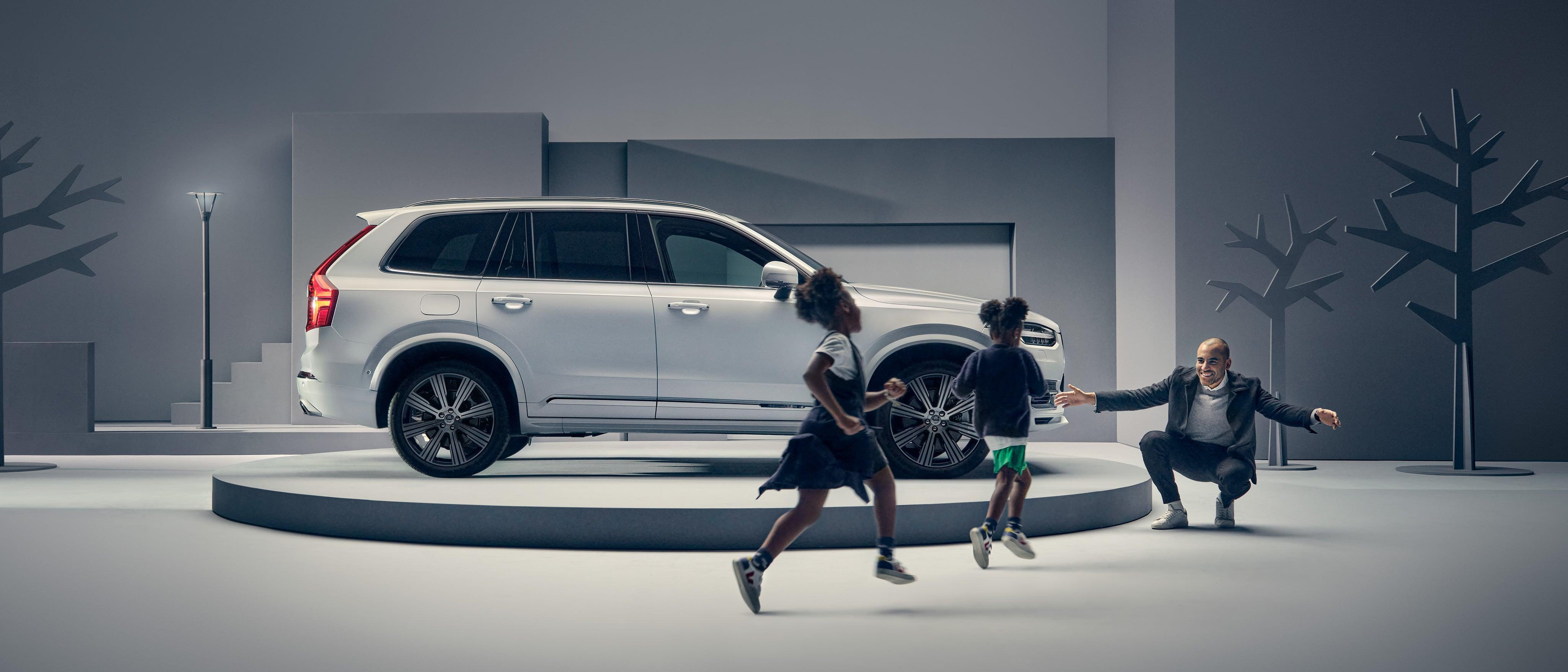 Ein Mann grüßt zwei Kinder vor einem Volvo auf einem Podest.