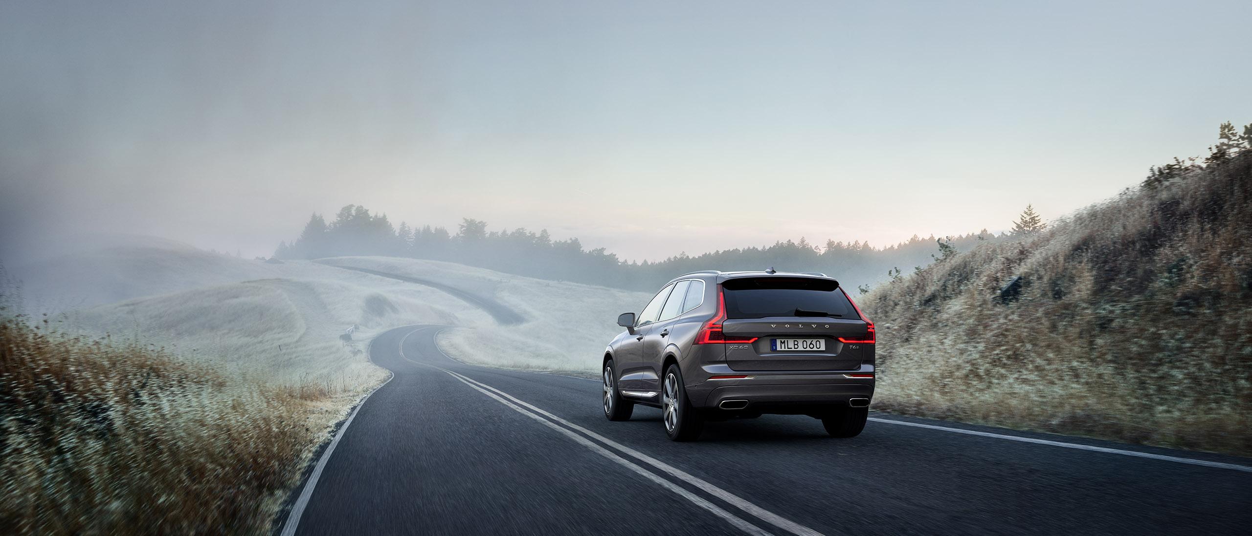 Ein grauer Volvo XC60 fährt in der Morgendämmerung auf einer Landstraße inmitten von Feldern