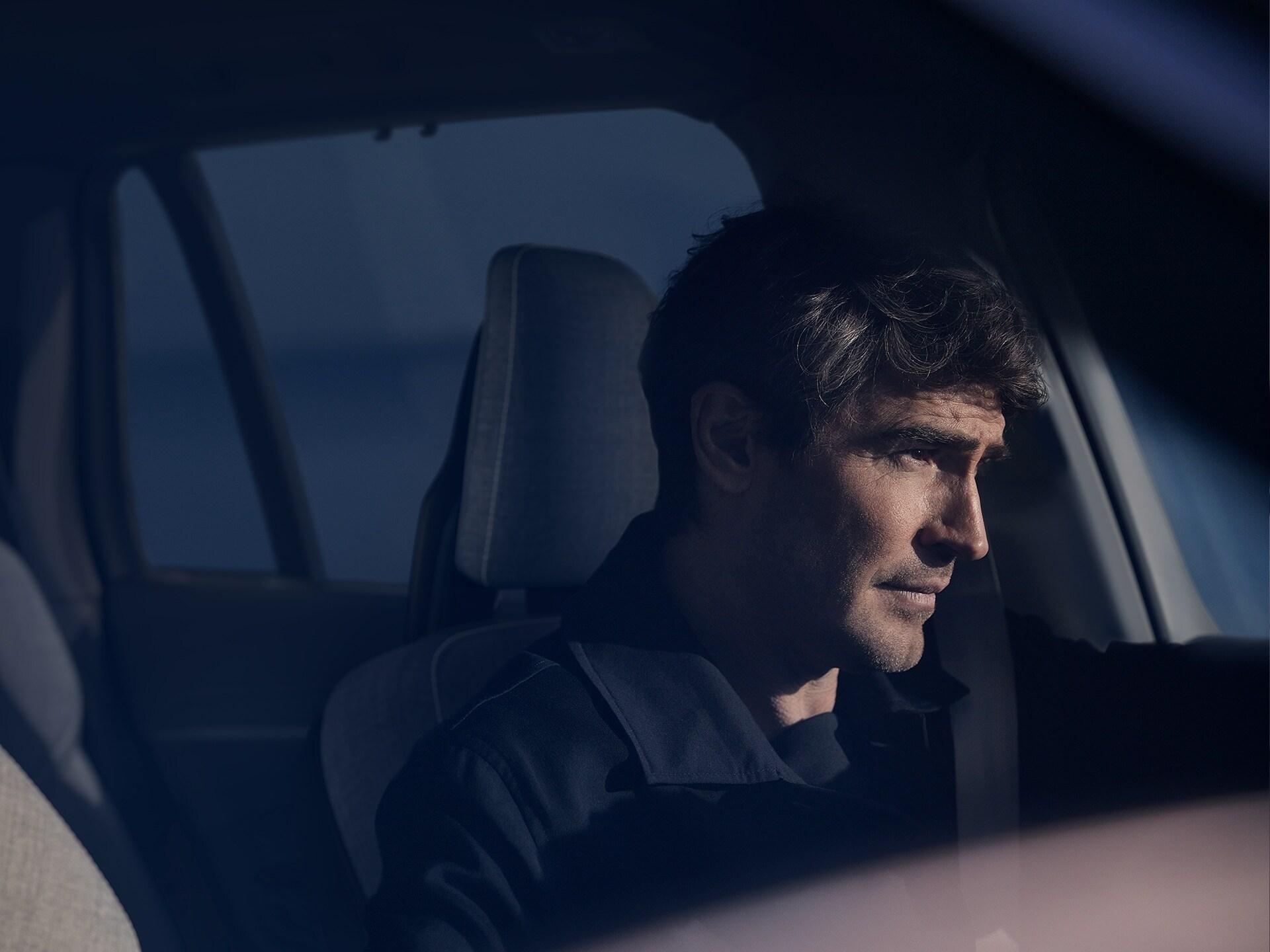 Ein Mann mit braunem Haar sitzt in einem Volvo XC90 Recharge, während die Sonne auf sein Gesicht scheint.