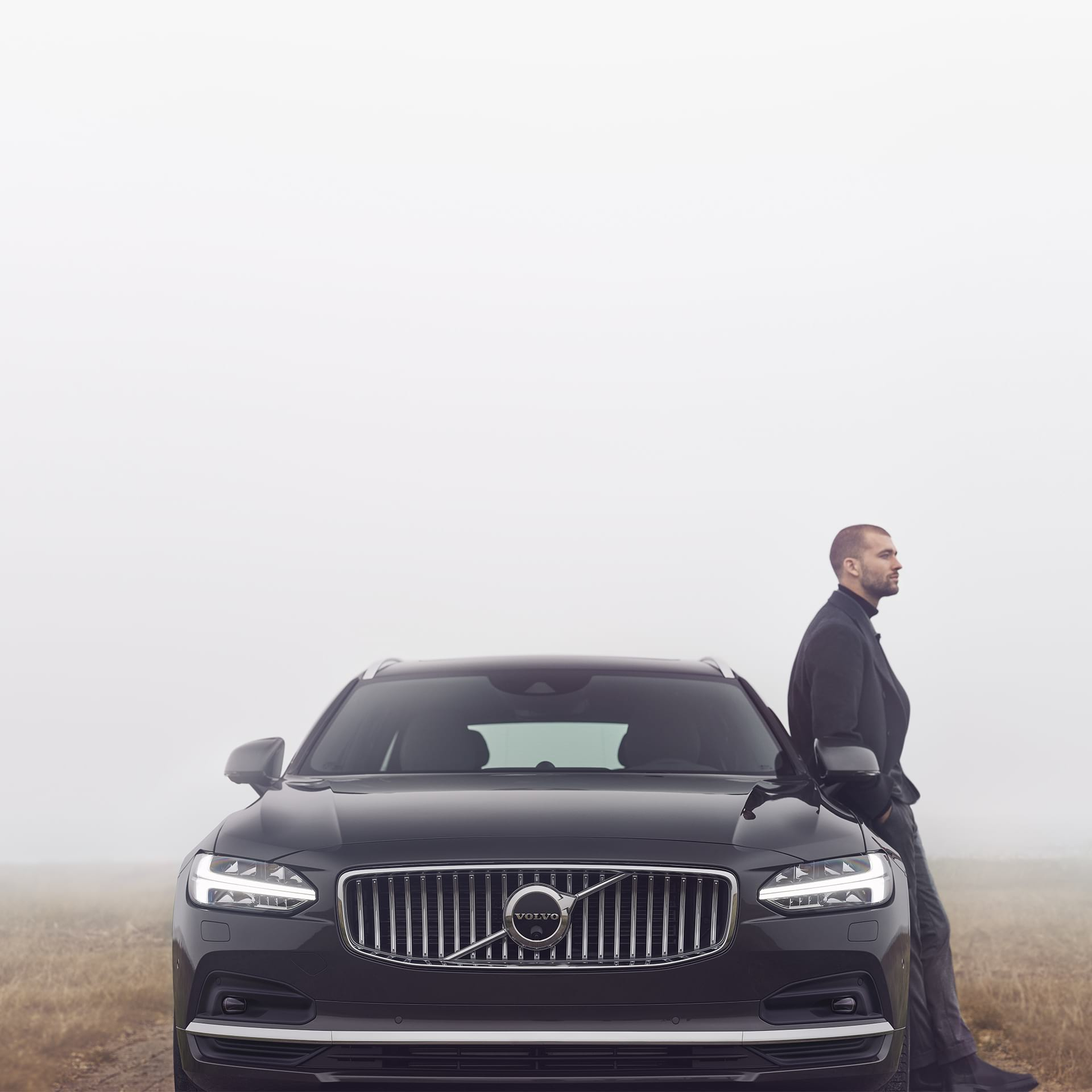 A man is leaning against his Volvo V90, it's cloudy outside