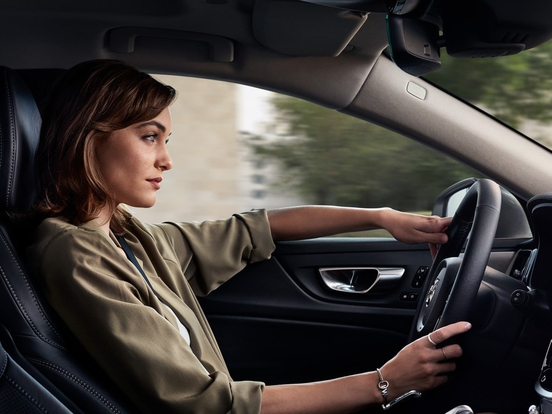 A lady inside Volvo Car holding the steering wheel