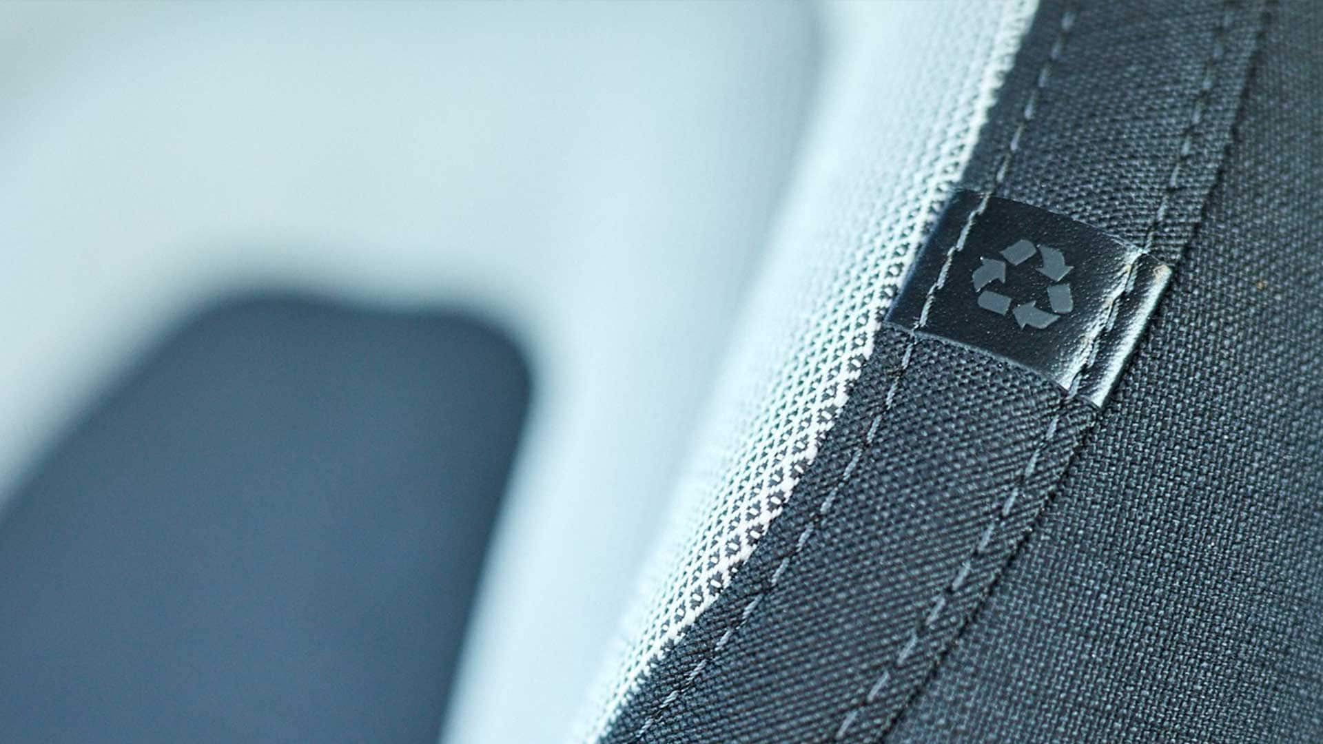 Close-up of a car seat with the universal recycling symbol attached to the fabric.