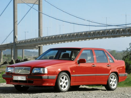 A red Volvo 850 standing in front of a bridge.