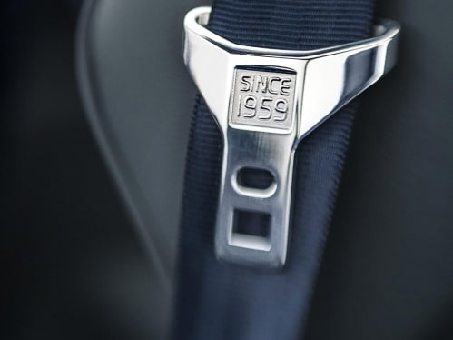 "A safety belt in grey with the text ""Since 1959"" engraved on the buckle."