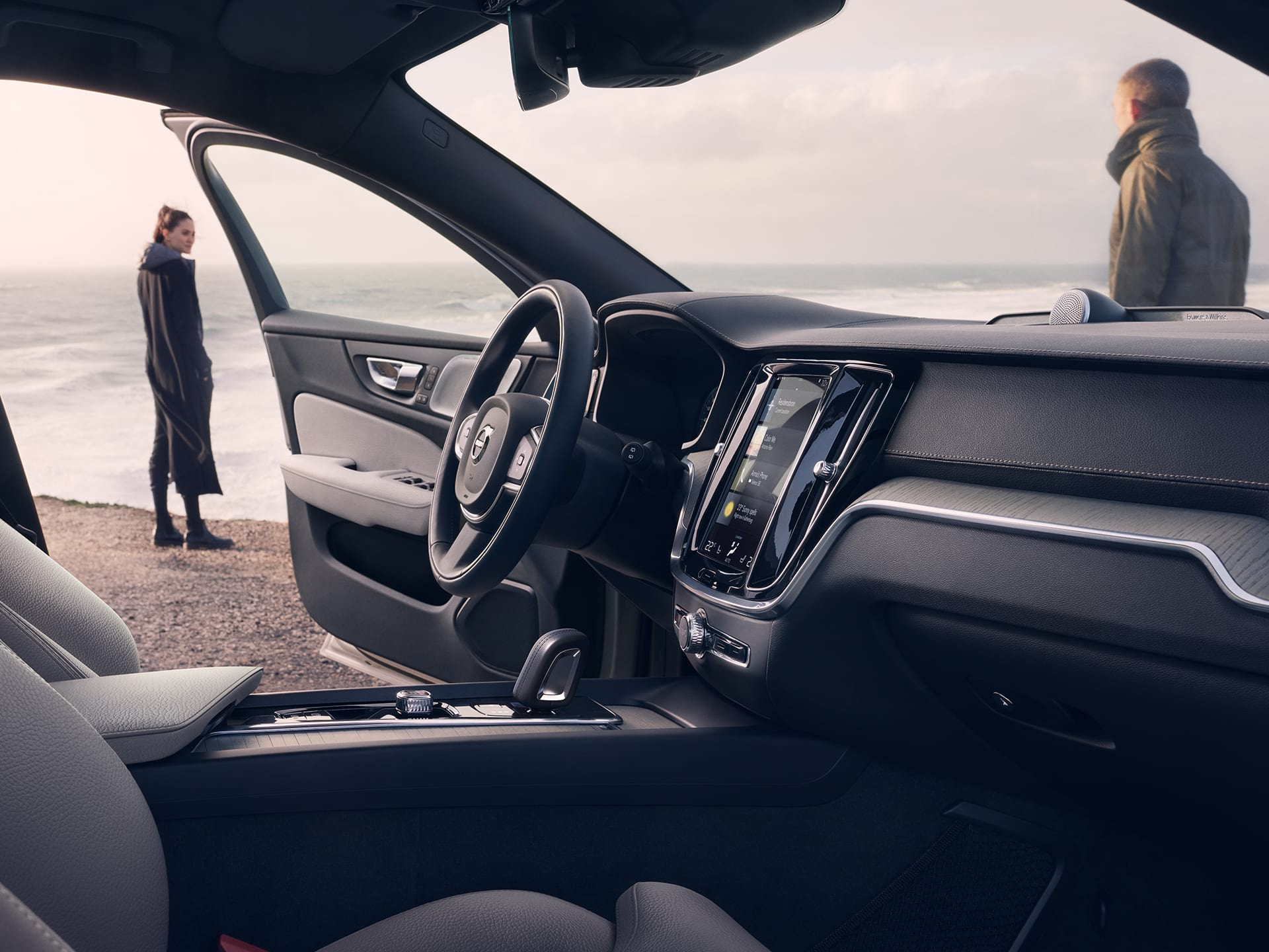 A woman stands on a beach, her V60 Cross Country has one door open.