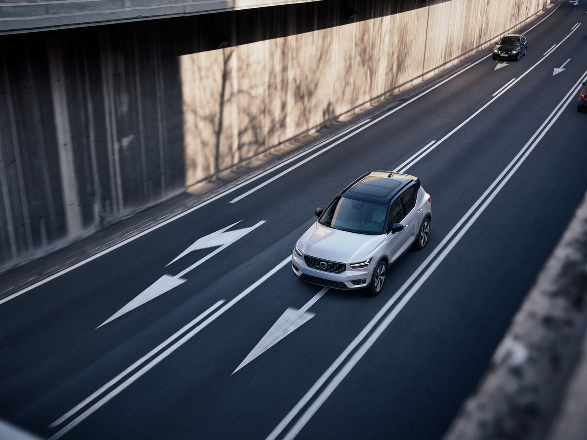 A white XC40 driving on a multi-lane road supported by driver assistance technology.