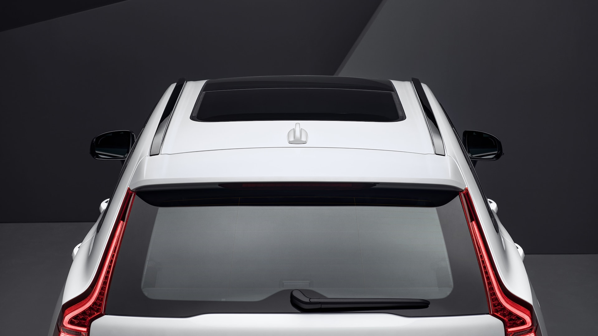 A white XC60 from above with an open-and-tilt panoramic roof