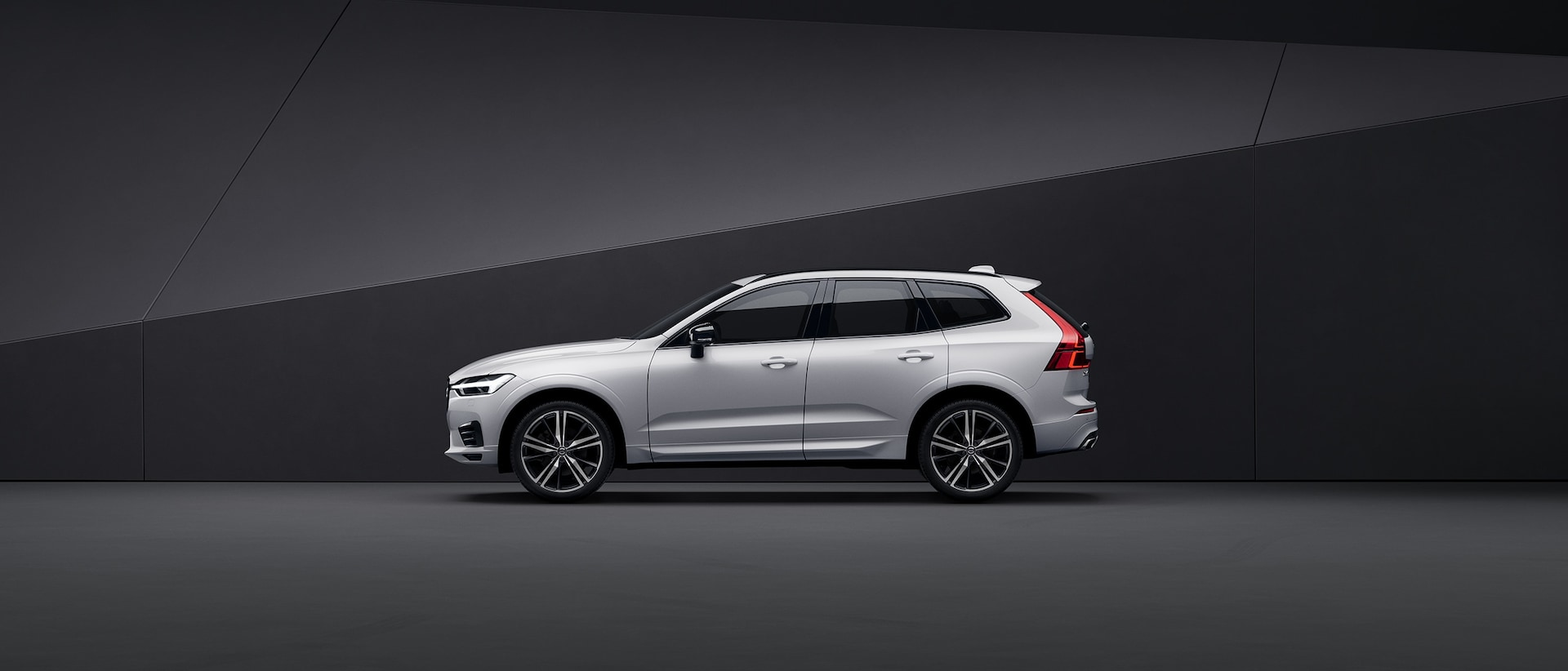 A white Volvo XC60 parked in a black surrounding