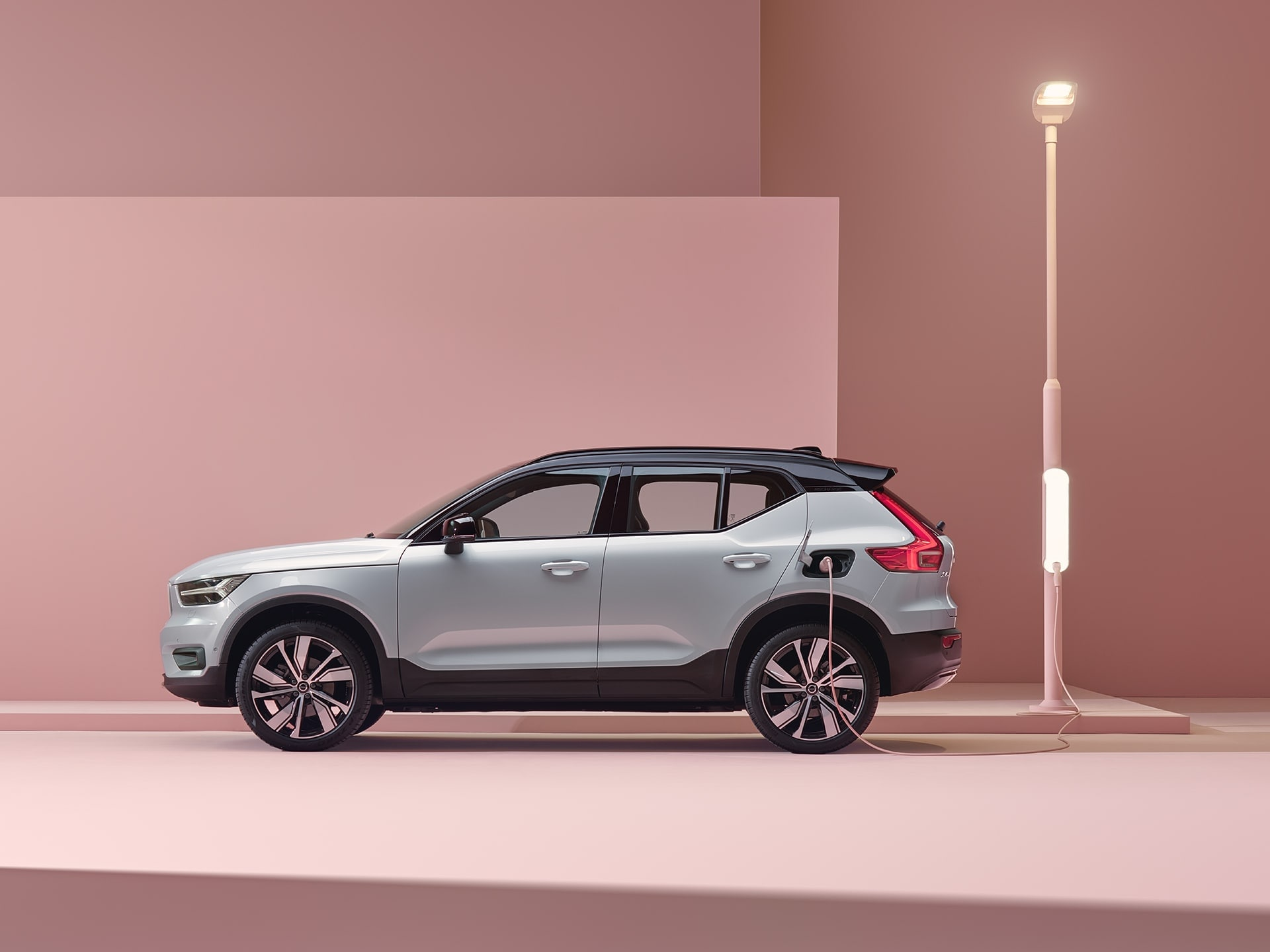 A glacier silver Volvo XC40 Recharge electric SUV charged in a pink city.