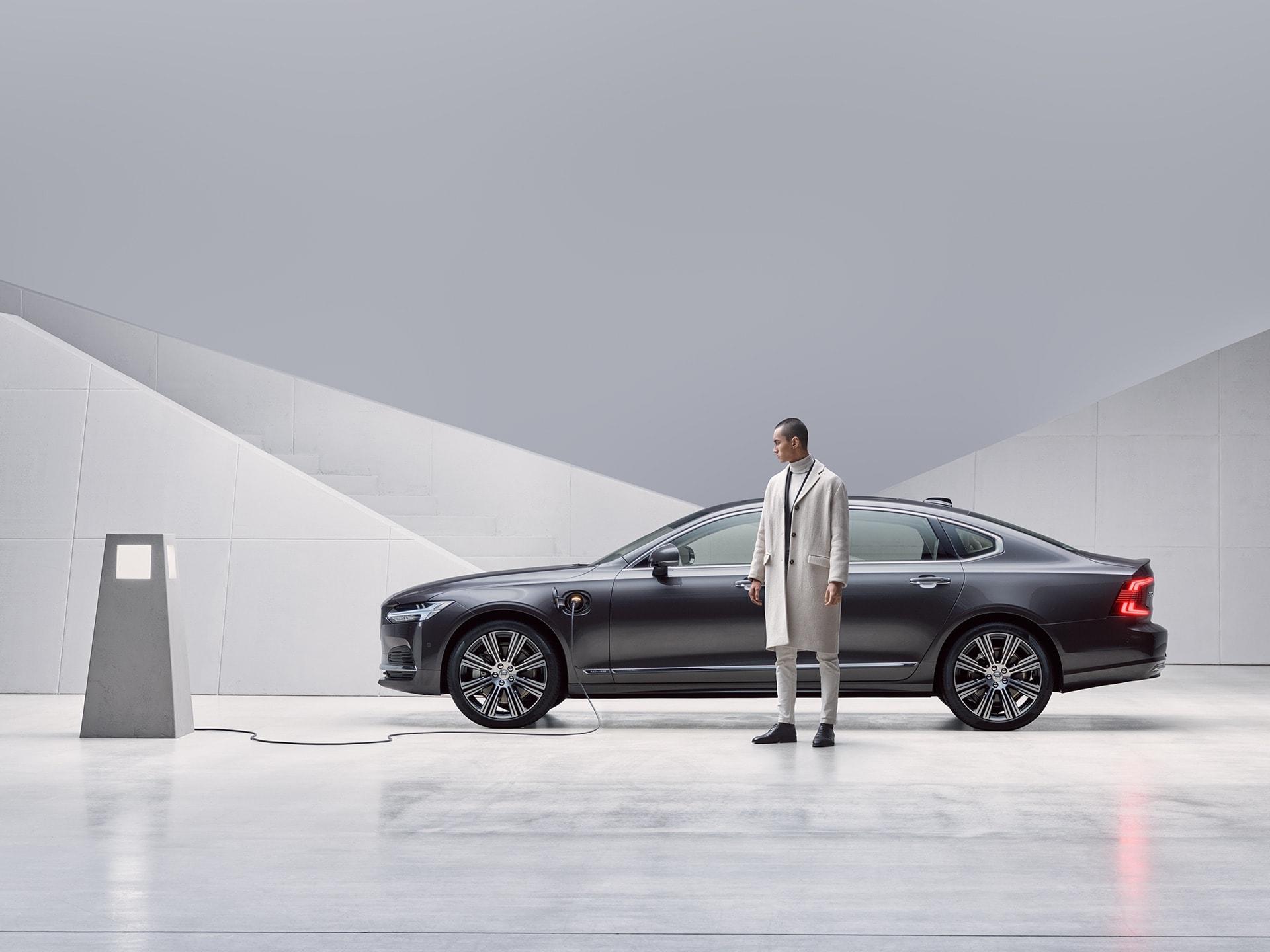 Kişi şarj olunan boz rəngli Volvo S90 Recharge avtomobilinin qarşısında dayanıb.
