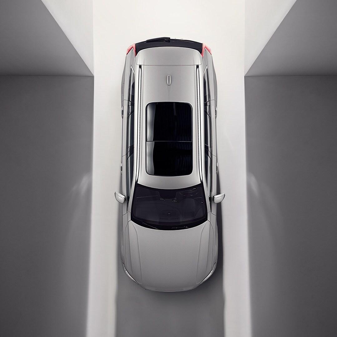 Açıq və qaldırılan panoramik dam örtüyü ilə Volvo XC90 Recharge avtomobilinin yuxarıdan görünüşü.